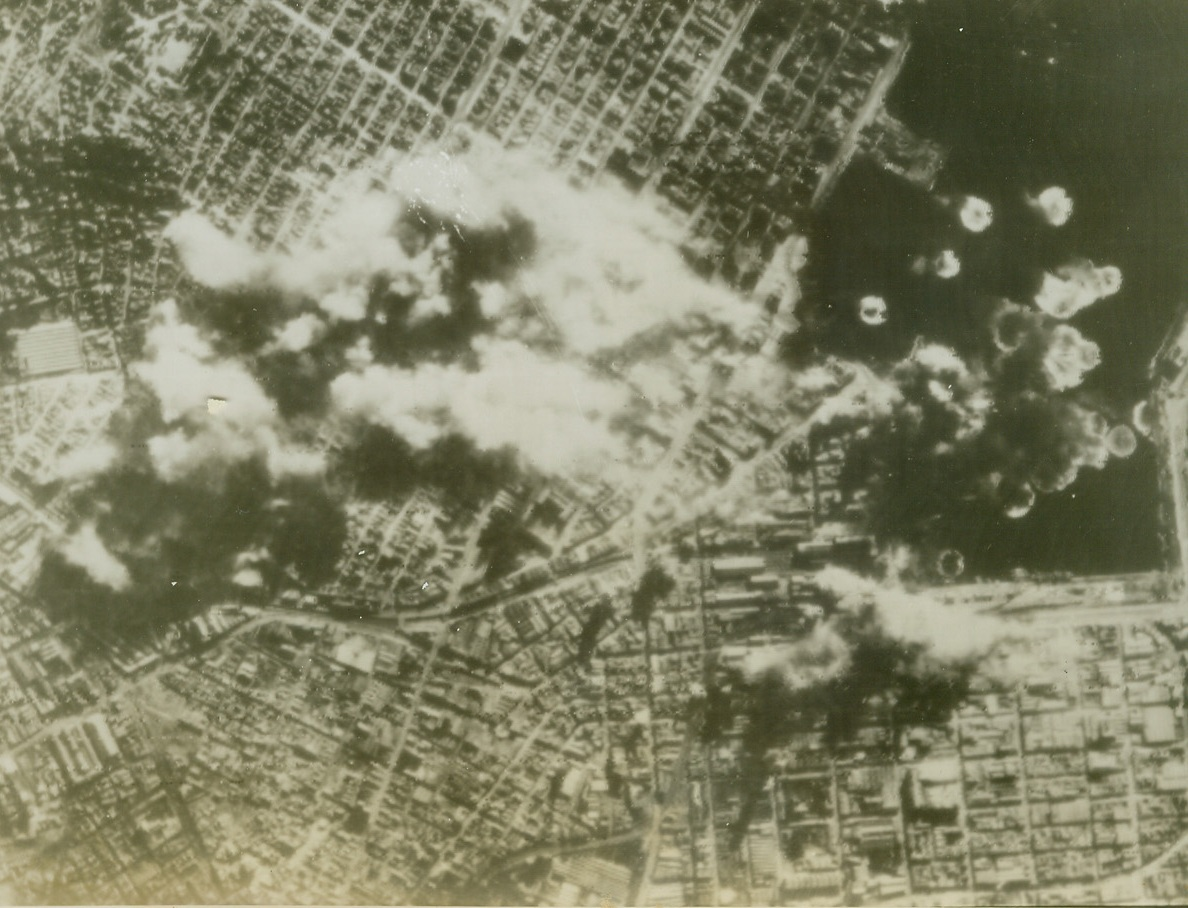 U.S. Bombers Slug Port of Athens, 8/15/1944. ATHENS, GREECE – Smoke shrouds the already battered dock area of Athens as U.S. Flying Fortresses bomb the vital Nazi supply center, on January 11th. Bomb-bursts dot the harbor waters as the B-17's of the 15th United States Army Air Force wing over their target. Credit (U.S. Army Air Force Photo Via OWI Radiophoto from ACME);