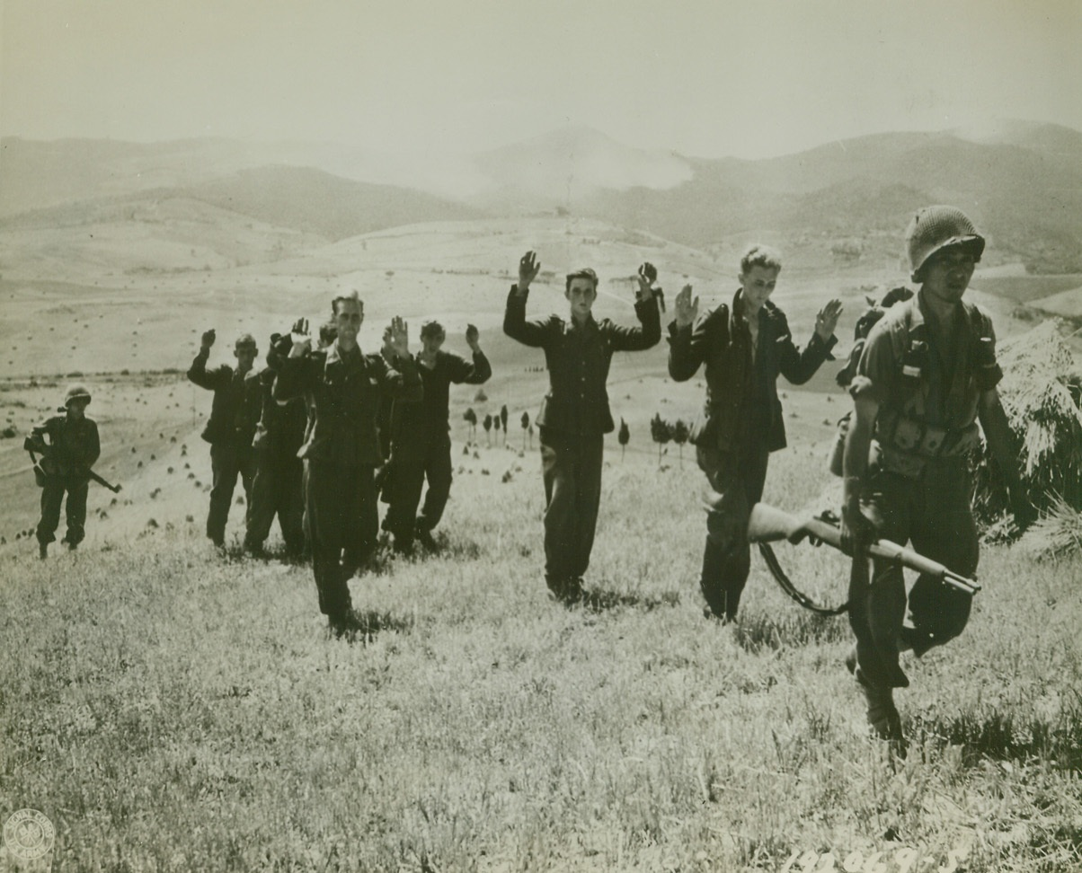 Hands Up – Give Up, 8/7/1944. ORCIANO, ITALY – Holding their hands high, German storm troopers follow their American captors after a short but sharp exchange of fire in the Orciano area. The enemy warriors surrendered to the riflemen of the 100th Infantry Battalion – Americans of Japanese ancestry. Credit Line (Official U.S. Army Photo from Acme);