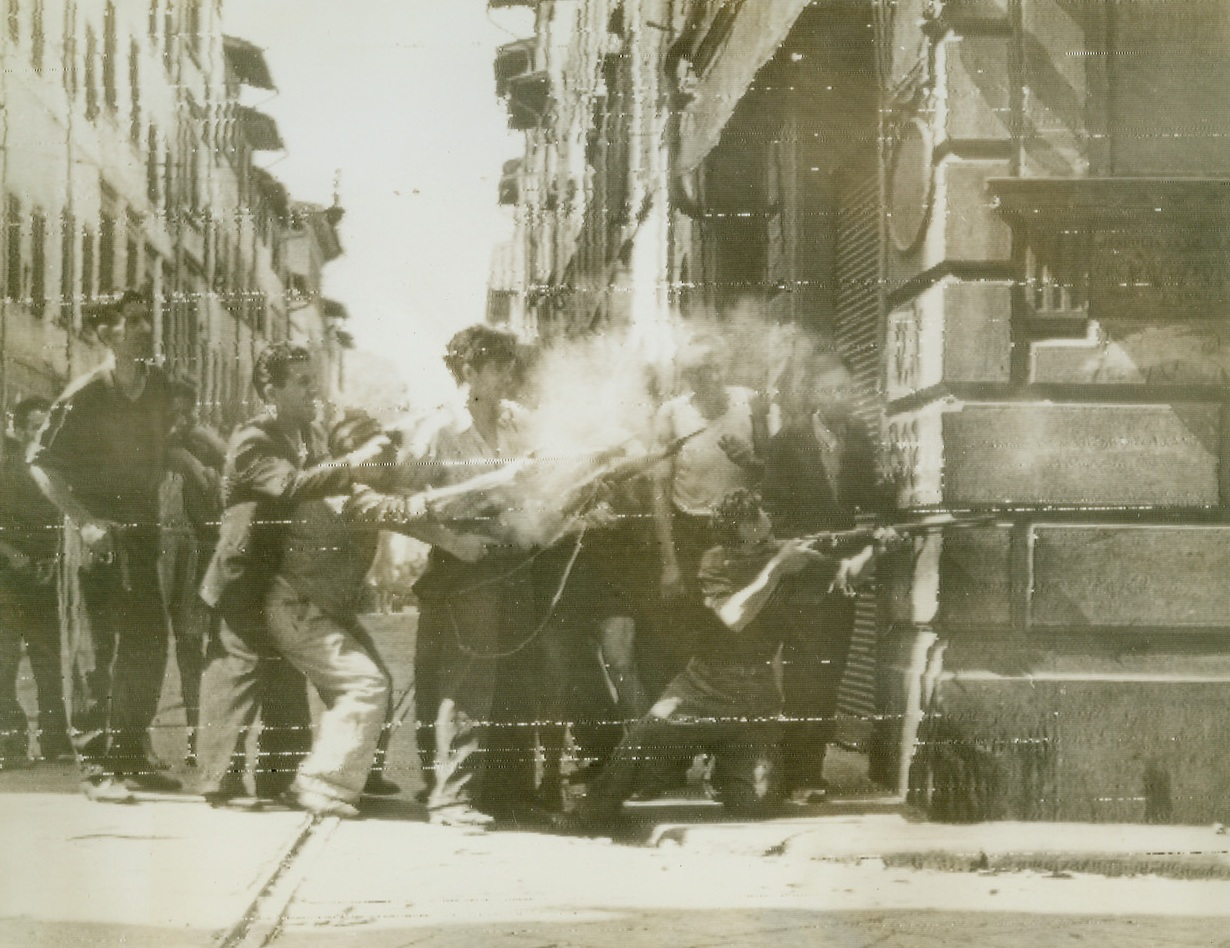 Street Fighting in Florence, 8/8/1944. FLORENCE, ITALY – As units of the South African troops of the British 8th Army enter the outskirts of Florence, hub of the Germans last defense line in Italy, anti-fascists lean out from the shelter of a building and fire around a street corner at German forces within the city. These civilians have given great aid in stemming the fighting of German and Fascist snipers.Credit (British Official Radiophoto via OWI from Acme);