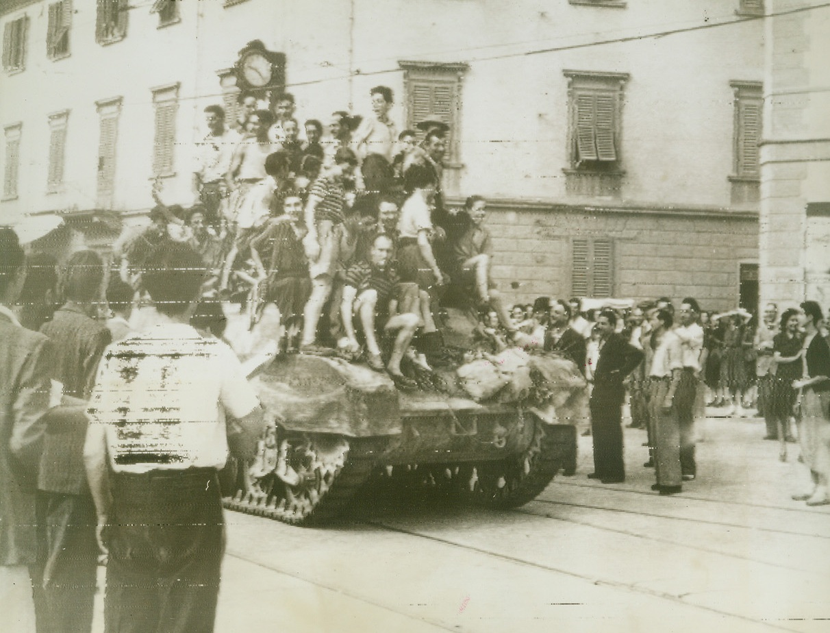 Florentines Welcome British Army, 8/8/1944. FLORENCE, ITALY – Jubilant youngsters jump atop a British tank as the people of Florence fill the streets to welcome a unit of the British 8th Army entering the city's outskirts. Clock in the background reads 9:25. Credit (British Official Radiophoto via OWI from Acme);