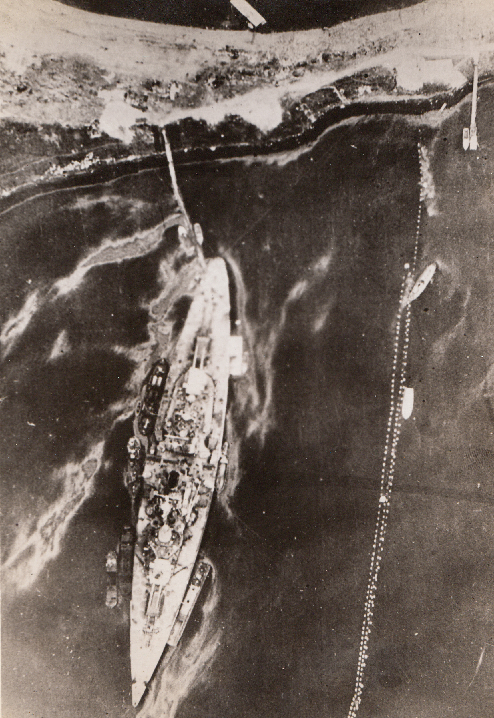 Twice-Damaged Tirpitz, 8/12/1944. NORWAY – This recent photo of the Tirpitz at her moorings in Kaafjord, Norway, was taken by an RAF reconnaissance plane of the Coastal Command. The ship was damaged in Kaafjord on two occasions, once by British submarines on Sept. 22, 1944, and again by Fleet Air Arm attack on April 3, 1944. Some of the damage has evidently been repaired, but the starboard boat and aircraft crane are missing.;