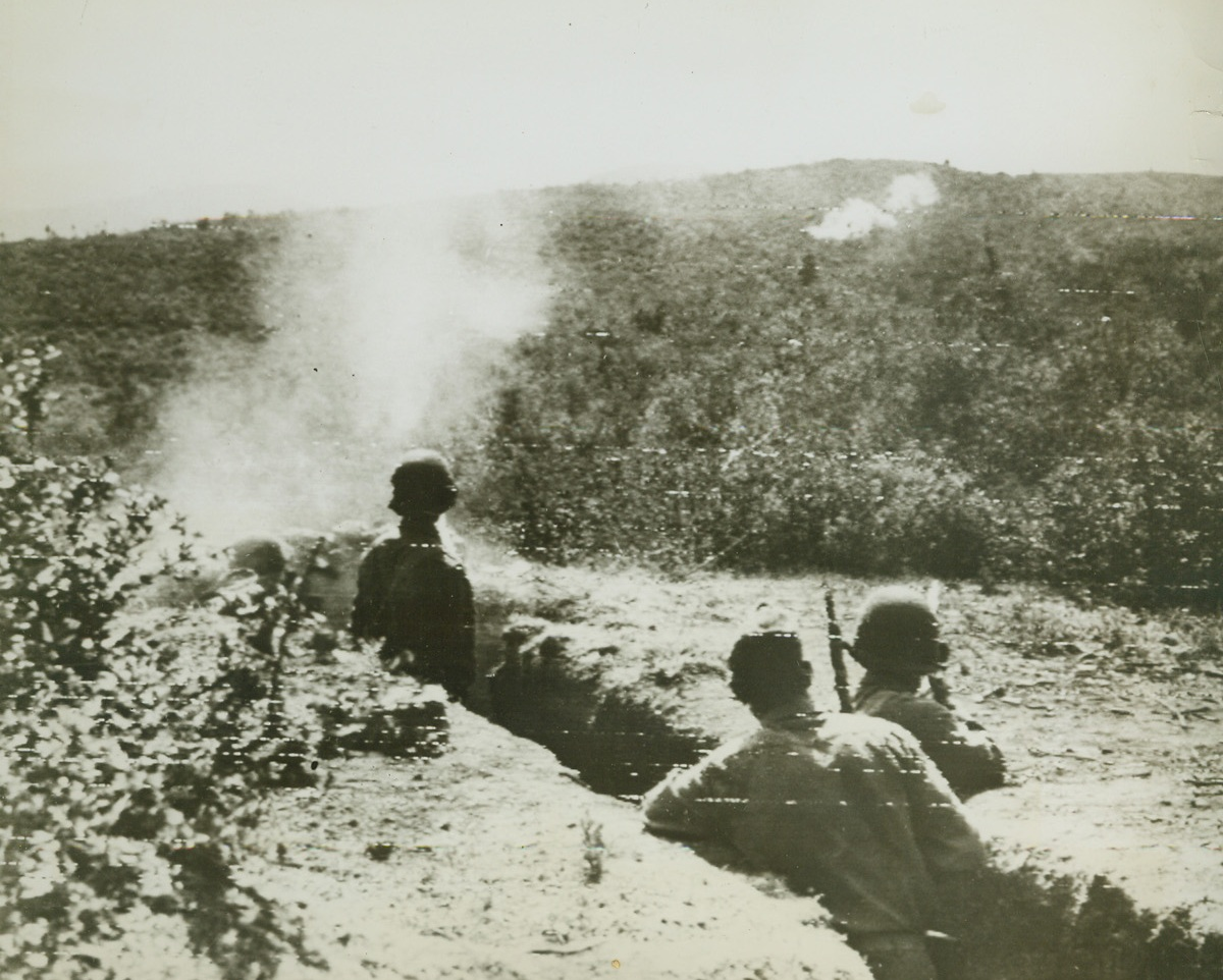 Jap-Americans Fight in Italy, 8/14/1944. ITALY – Proving their loyalty on the battle front are these two Jap-Americans fighting in Italy. Combing for snipers, Pvt. Veikichi Arakaki, from Koloa Kauai, T.H. (Hawaii), and a buddy at left, fire rifle grenades into the hills. Bursts can be seen on the hillside.Credit (Signal Corps Radiotelephoto from Acme);