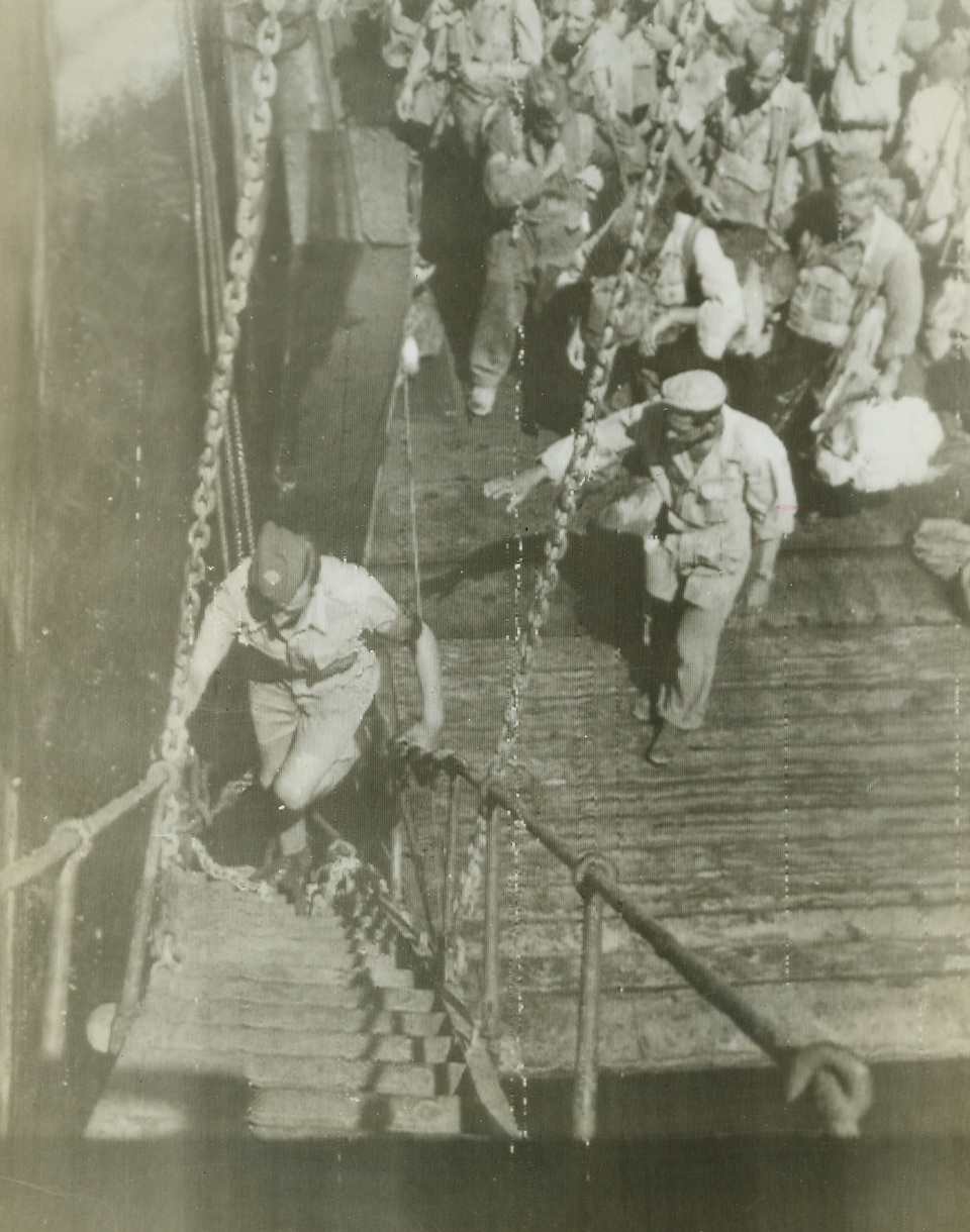 On Their Way to France, 8/15/1944. ITALY – Walking up the gang-plank as his comrades wait their turn on the dock below, a ground crew member of the Royal Air Force boards a vessel at an Italian port headed for the new invasion front in southern France.Credit (OWI Radiophoto from Acme);