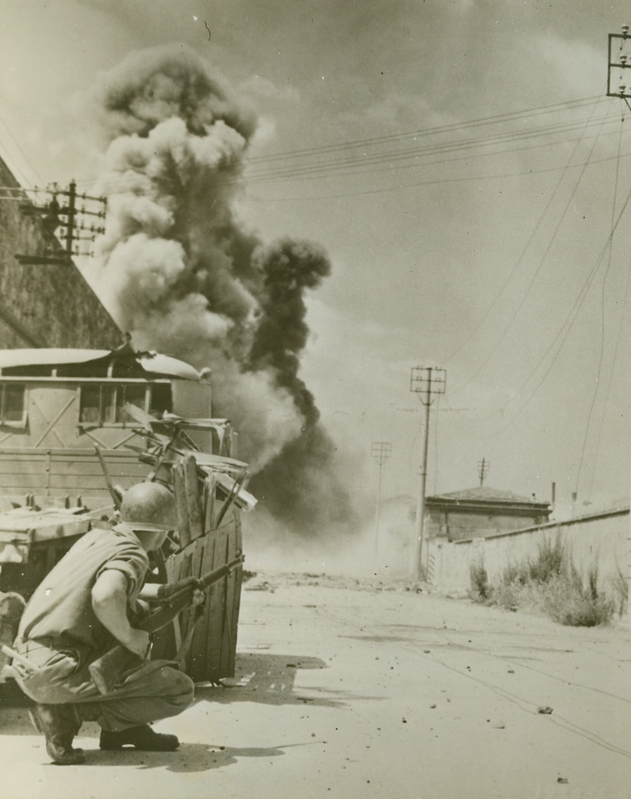 Enemy Mines Go Up, 8/7/1944. LEGHORN, ITALY – Taking cover behind a tank, Cpl. Duane T. Moen, Minneapolis, Minn., is on the alert for snipers as his Fifth Army buddies set off mines sowed heavily in one of the main streets leading to Leghorn harbor. A giant column of smoke rises in background as the mines blow up.Credit Line (Official U.S. Army Photo from Acme);