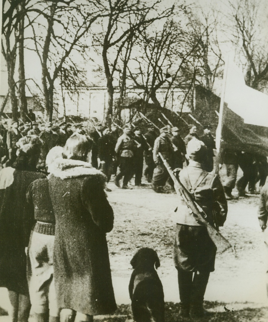 Polish Patriots on Parade, 8/23/1944. POLAND – After church services celebrating Poland's National Day (May 3rd), Polish guerilla fighters troop past their colors in a town 120 miles southwest of Warsaw. The patriots are members of the Nrubieszow (Podleze) battalion of their country's home army. Photo obtained through a neutral source.Credit Line (Acme);