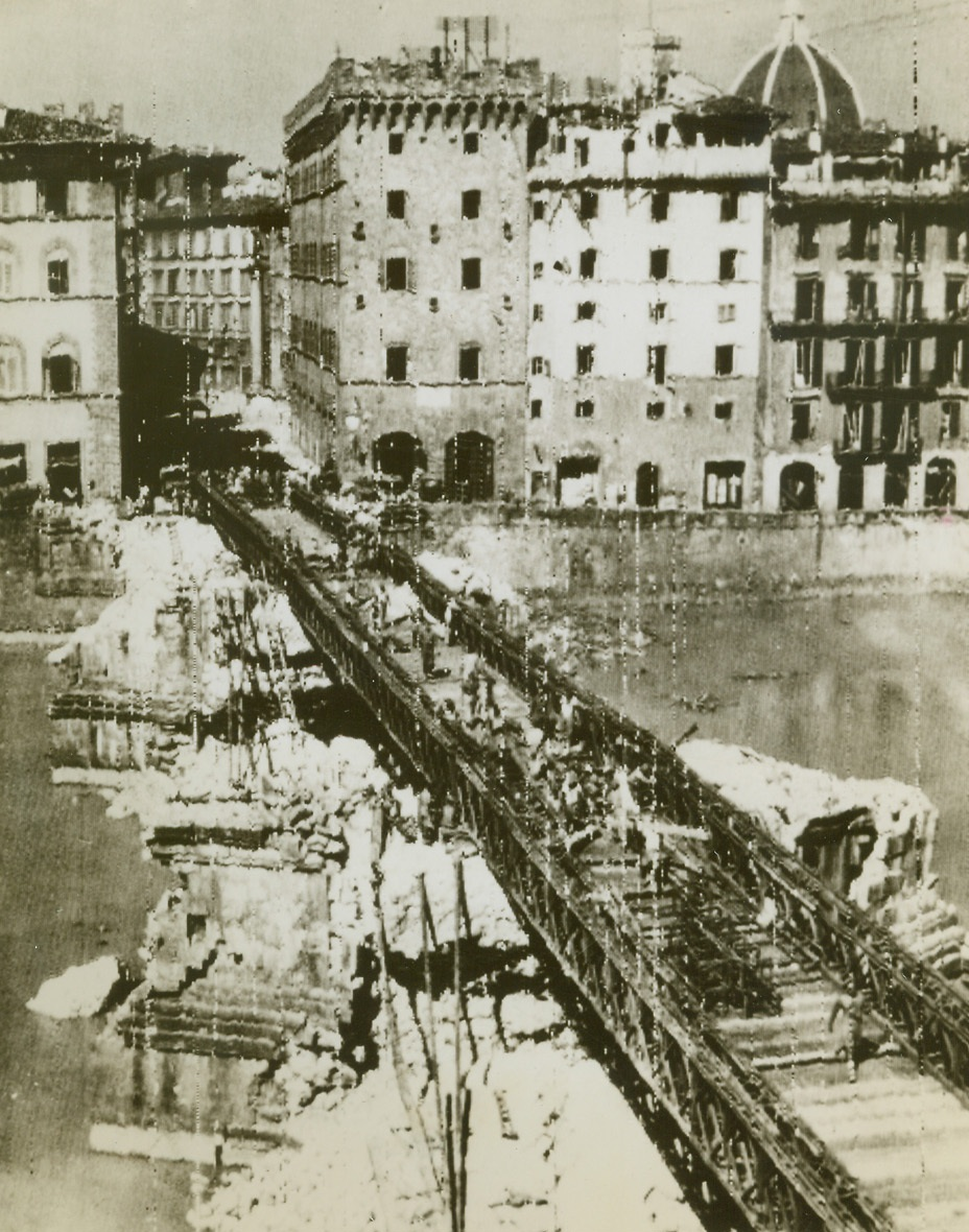 Bridge Florence Canal in Record Time, 8/19/1944. ITALY – Working with terrific speed, men of the Royal Engineers astounded the people of Florence by replacing the destroyed Ponte San Trinita with a Bailey Bridge in record time. Bridge was built on the piers of the wrecked span. Except for a few entrenched Nazi snipers, the ancient city is now completely in Allied hands. Photo by British Army Film Unit. Credit (OWI Radiophoto from Acme);