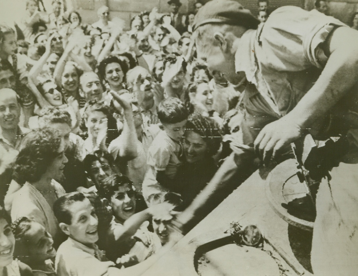 Welcome to Florence, 8/7/1944. FLORENCE, ITALY – Waving and smiling their greetings to the Allied Liberators, joyous Florentines welcome victorious troops at the southern outskirts of their city. A member of a South African tank crew leans down to shake friendly hands.Credit (Signal Corps Radiotelephoto from Acme);