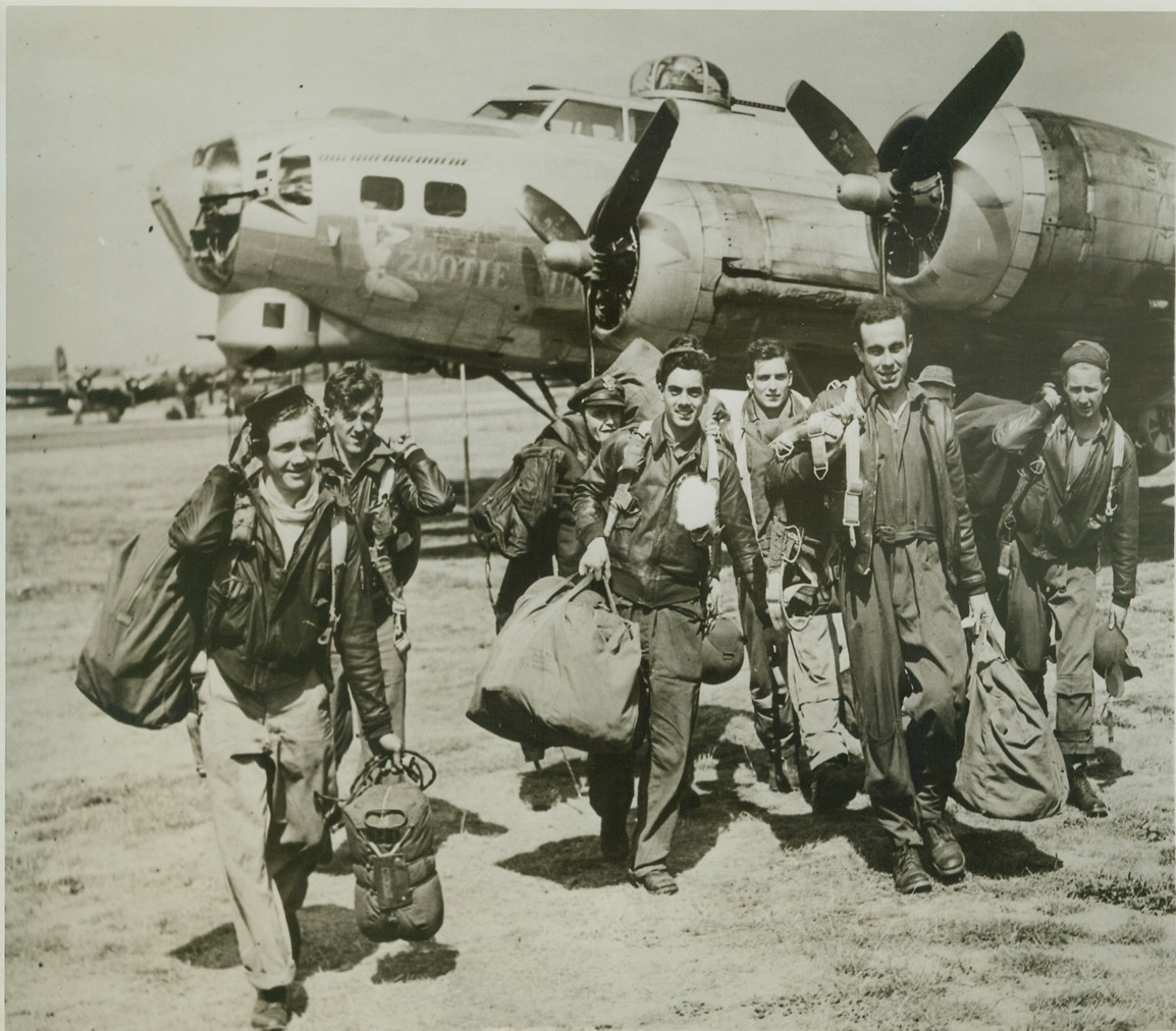 Yank Return from Raid, 8/22/1944. ENGLAND -- American airmen walk from their Fortress bomber on returning to their base in Britain after raiding strategic targets in Alsace Lorraine. They are (left to right): T/Sgt. Harry Soderburg, Lueders, Tex.; T/Sgt. Fernand Savasuk, Winslow, Me.; 1st Lt. Richard Davies, Congers, N.Y.; S/Sgt. Bernice Stanton, Cookville, Tenn.; 2nd Lt. Joseph Hughes (rear), Pittsburgh, Pa.; 2nd Lt. Harry Neumann, Union City, N.J.; S/Sgt. Raymond Glasser, Little Sioux, Iowa; Sgt. Mervin Wingard (rear), Kittaning, Pa.; and Sgt. Bill Baker of Chanute, Kansas. Credit: (ACME);