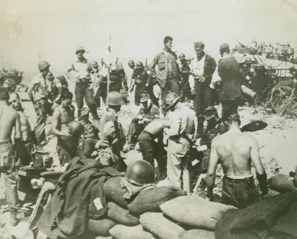 FIRST AID FOR FRIEND AND FOE, 8/16/1944. U.S. Infantrymen and German prisoners receive medical treatment from American corpsmen at a beach dressing station in Southern France, while (background), Yank troops file by on their way to consolidate the new beachhead. Credit: Acme photo by Sherman Montrose for War Picture Pool via Army radiotelephoto;