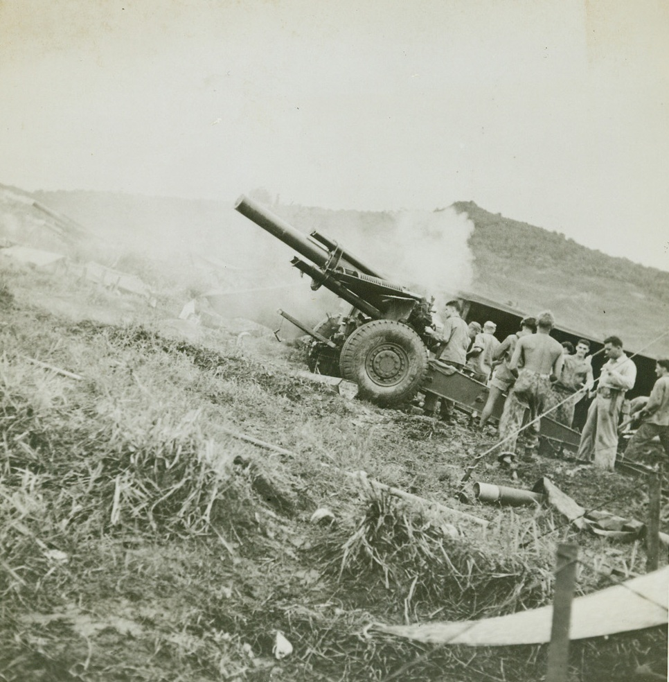 BLAST JAPS OFF GUAM, 8/11/1944. GUAM—A Marine howitzer, one of the first to be brought ashore, blasts enemy positions in the battle for Guam, the first American base to be taken by the Japs and the first to be recovered from them. More than 10,000 Japanese were killed in the fighting for the island. Credit: U.S. Navy photo from Acme;