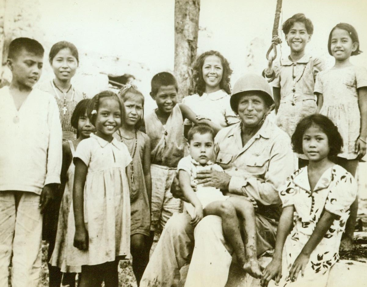 Benevolent General, 8/12/1944. Guam – Smiling Maj. Gen. Roy S. Geiger, USMC, commander of US Expeditionary Forces on Guam, holds one sober-faced native child on his lap, while others surround him, grinning cheerfully. The children were rescued from the Japanese by American forces 8/23/44 Credit (ACME);