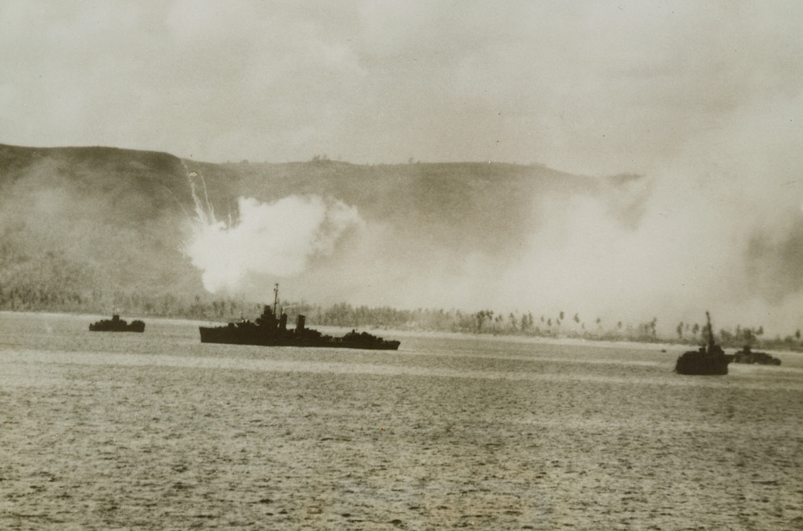 Fire and Brimstone on Guam's D-Day, 8/2/1944. Guam Is. – A phosphorus shell explodes in a burst of burning fog, and US ships move into the harbor at Guam as landing assaults are launched against the Japanese stronghold. The landings were preceded by aerial and surface bombardment.Credit: US Navy photo from ACME;