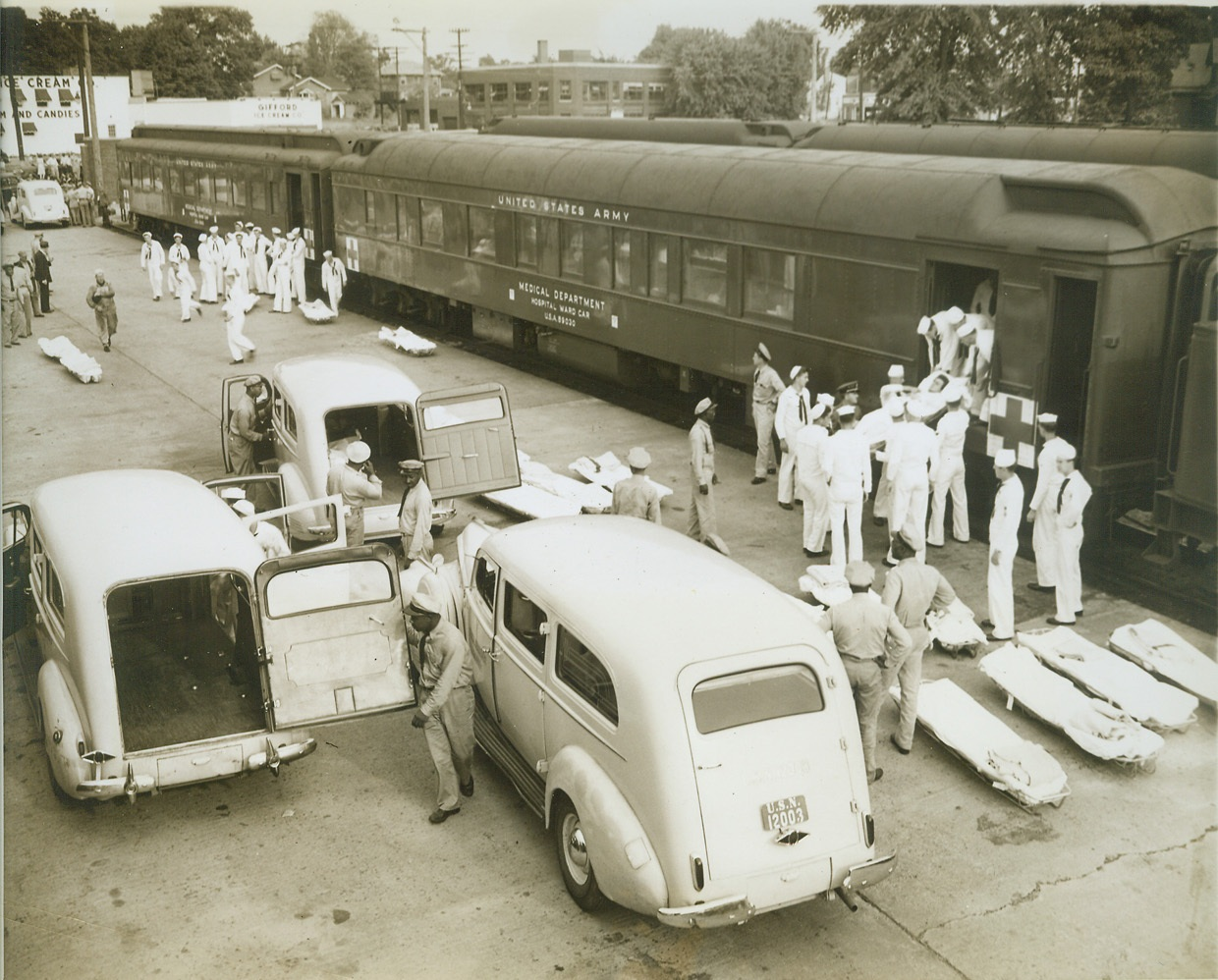 Navy's Normandy Wounded Brought Home, 8/2/1944. WASHINGTON, D.C. -- With ambulances and stretchers waiting, some of the one hundred and twenty nine Navy men wounded in Normandy are lifted from a hospital train which carried them to Silver Springs where they will receive further treatment in the Naval Medical Hospital. These Naval heroes were brought across the Atlantic from France in a hospital ship. Credit: (ACME);