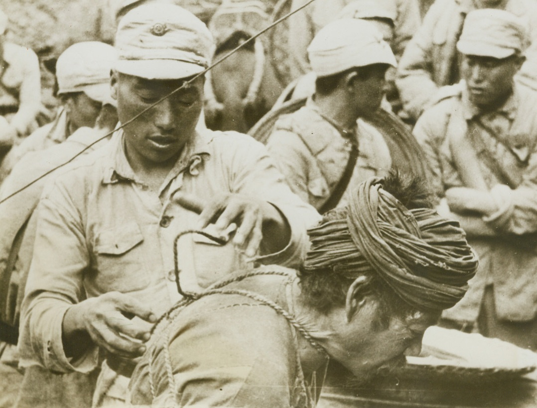 Up for Trial, 8/21/1944. China – Suspected of being a Japanese spy, this peasant is untrussed by a Chinese warrior at Division Headquarters on the Salween River front. Although he will be given a fair trial, the suspect will receive little sympathy from the Chinese if he is proven guilty. Jap spies are quickly disposed of by Chinese forces fighting to reopen the Burma road. Credit: Signal Corps photo from ACME;
