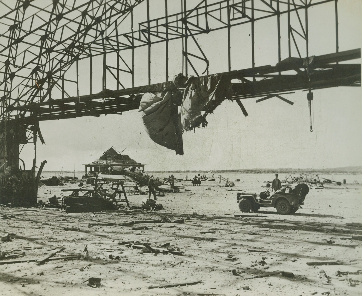 After Yank Bombardment, 8/11/1944. TINIAN – Pre-invasion naval and aerial bombardment completely shattered enemy installations and equipment at this Jap airport on the Northern end of Tinian. Marine forces captured the field shortly after hitting the beach and reconstruction of the strip is already underway. Credit: Marine Corps photo from ACME;