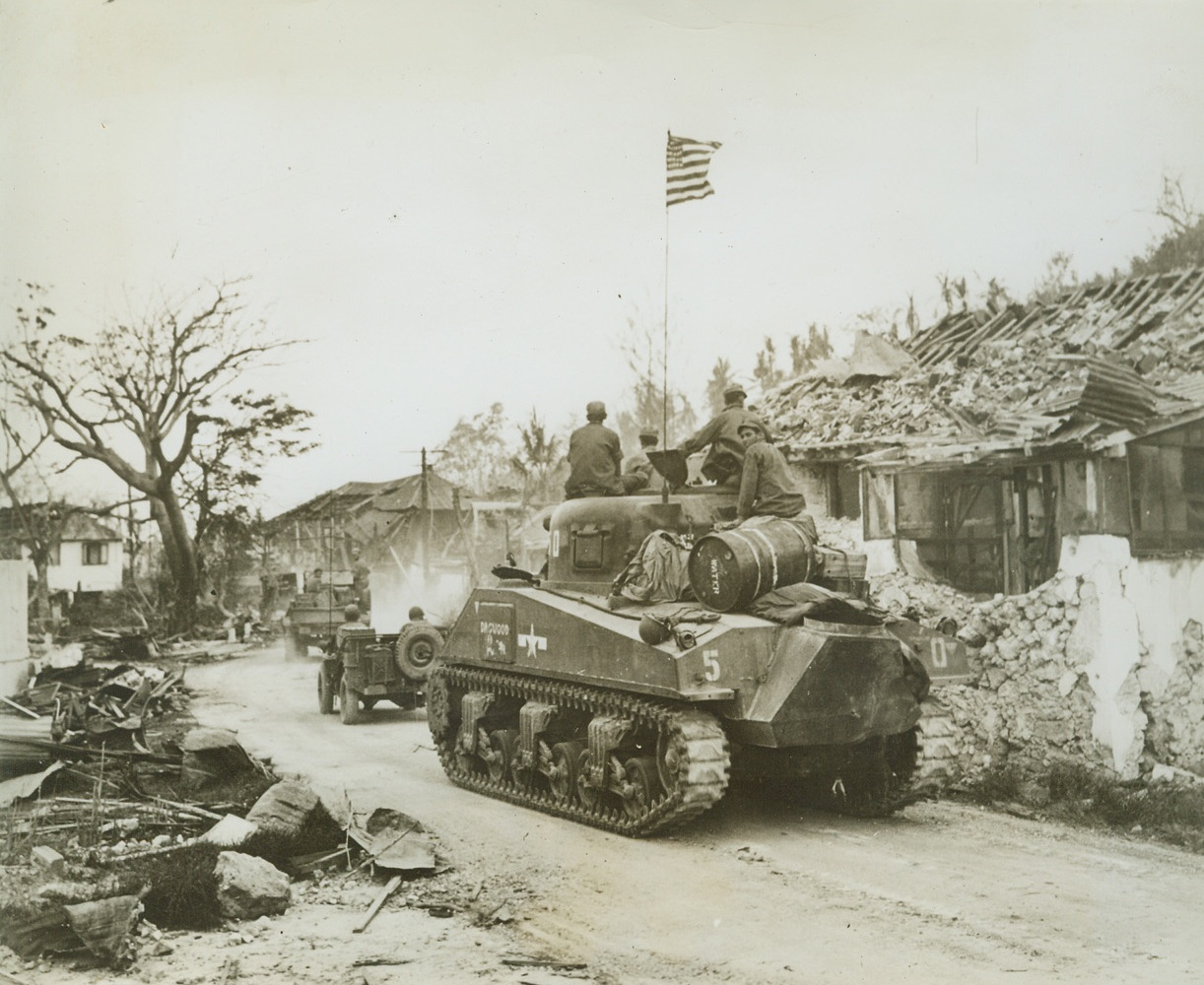 Old Glory Moves Up to Battle, 8/11/1944. GANA, GUAM – Moving through the war-shattered town of Agana, tanks and armored vehicles of the Third  U.S. Marine Division roll to the North on the hells of retreating Japs. They carry with them the American flag, to wave once again over the island that was seized by the Japs shortly after Pearl Harbor. Credit: ACME;