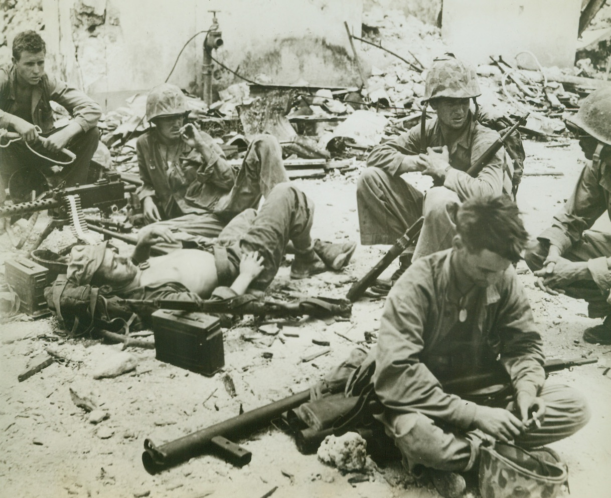 No Targets—Gun Crew Rests, 8/11/1944. AGANA, GUAM – When they ran out of Japs to shoot at on Agana, these gun crew members laid down their arms to relax for awhile, but they leave the cartridge belt in their gun—just in case. Left to right: Pfc. W. C. Dean, Meridian, Miss.; Pfc. R. A. Rouse, Cincinnati, Oh.; Pfc. E. J. Bernier (lying down), River Rouge, Michigan; and Cpl. T. L. McHugh, Cincinnati, Oh. Men in foreground and at extreme right are unidentified. All are of the Third Marine Division Credit: ACME;