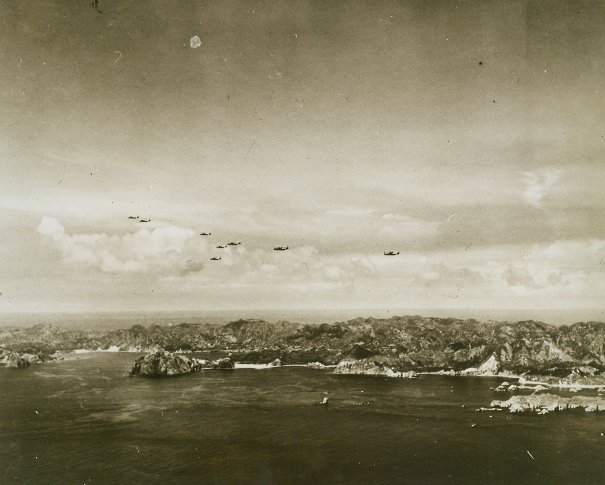 Navy Force Strikes in Bonins, 8/9/1944. BONIN ISLAND – Swift and deadly, eight Grumman Avengers of a hard-hitting Pacific fleet task force glide over the gnarled shoreline of Chichi Jima in the Bonin Islands, only 600 miles south of Tokyo. Our planes destroyed 13 Jap ships and 32 planes; they damaged more than 20 ships and 96 planes. Credit: Official U.S. Navy photo from ACME;