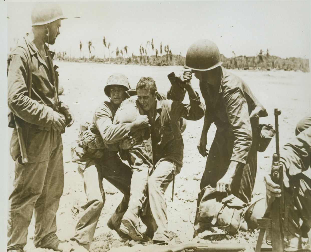 His Buddies to the Rescue, 8/6/1944. GUAM -- A Leatherneck swings a fellow Marine, who was hit by a Jap bullet in fierce fighting for an airstrip near Orote, to his shoulder and other Marines clear the way for him as they carry the wounded man back to an emergency station. Credit (ACME) (WP);
