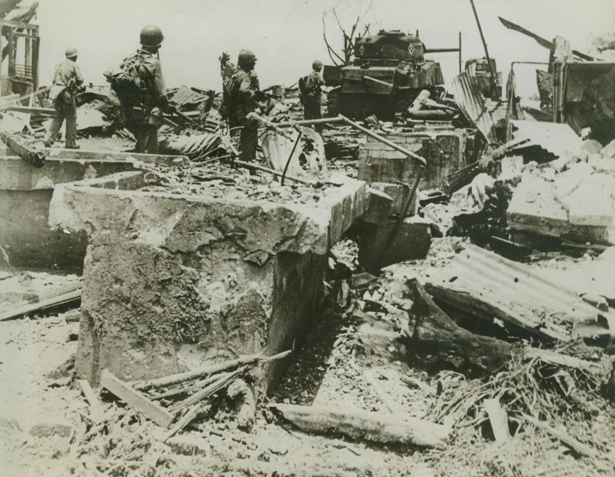Leathernecks Enter Former Marine Barracks, 8/6/1944. Guam – US Marines hold their guns cocked as they look for signs of Japs hiding amidst the ruins of the old Marine barracks on Guam. Moving in without opposition, they are the first men and tanks to enter the site, which has been almost completely destroyed by aerial and naval bombardment. Credit (ACME);
