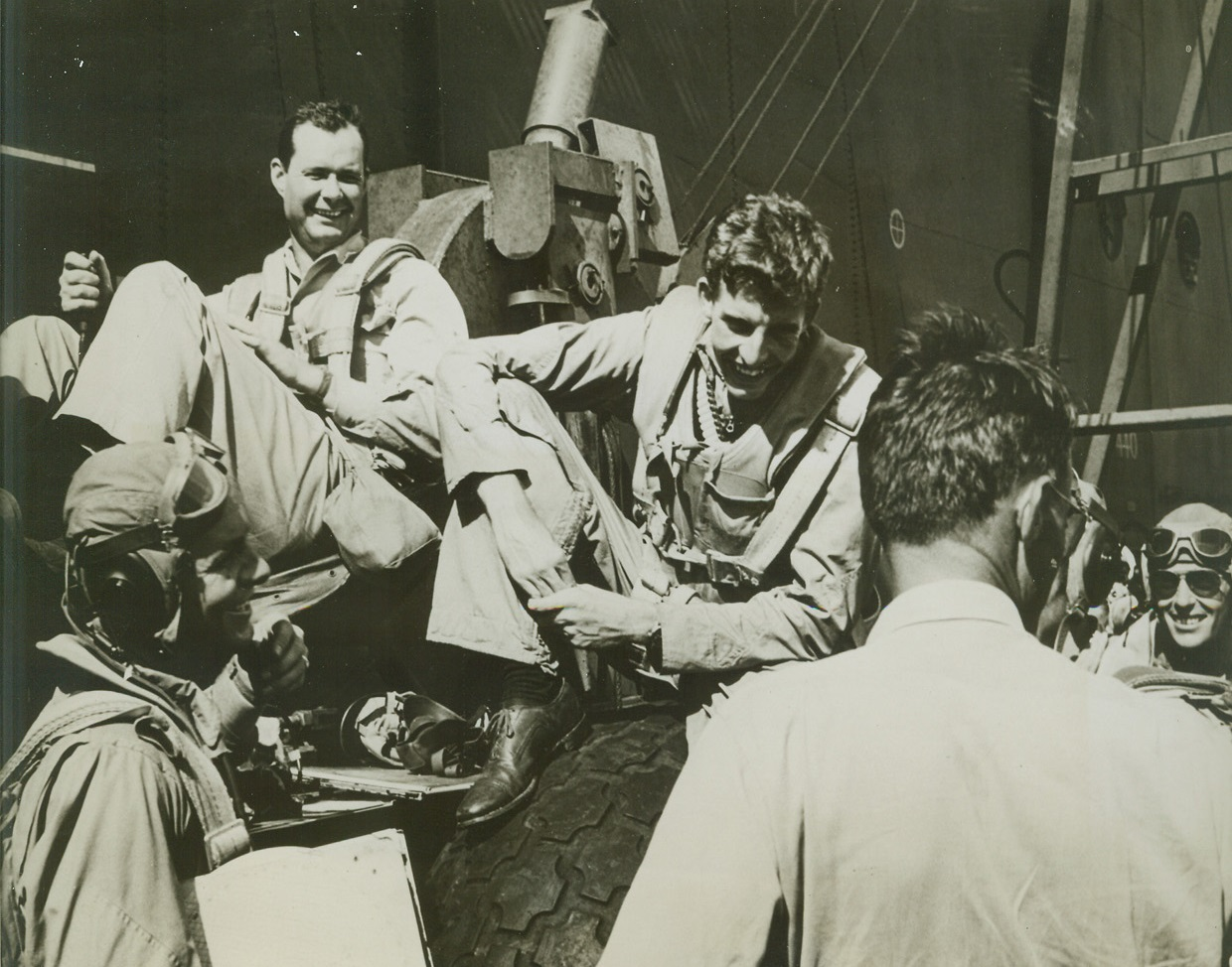 Rehashing Victory, 8/23/1944. At Sea – Relieved grins light the faces of air group 16 pilots as they discuss a victorious clash with Jap planes, after their return to their carrier.  Seated (top) are; (left to right) Comdr. P.D. Buie of Nashville, GA; and Ensign W.J. Seyfferle, Cincinnati, O.  Lower left: Ensign Edward G. Wendorf, West (co), Texas.  With back toward camera: Comdr. L.B. Southerland, USN.  Extreme right: Lt. (jg) Frances M. Fleming, Portland, Ore. Credit line (official U.S. Navy photo from ACME);