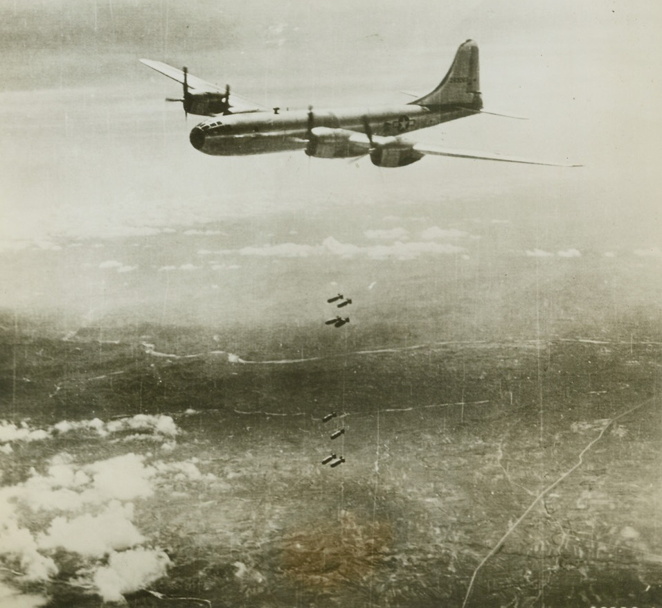 """Deadly """"Eggs"""" Drop on Jap Steel Center, 8/29/1944. Anshan, Manchuria – In this, one of the first pictures of the B-29 superfortresses in action over enemy territory, one of the bombers lets loose its load of explosives over the Showa steel works in Anshan in the July 29 raid.  The Showa steel works is the second largest integrated iron and steel plant in the Japanese system, and  a key unit in Japan's industrial development of Manchuria.  The results of the raid were good, with moderate enemy fighter and anti-aircraft opposition. Credit (official USAAF photo from ACME);"""