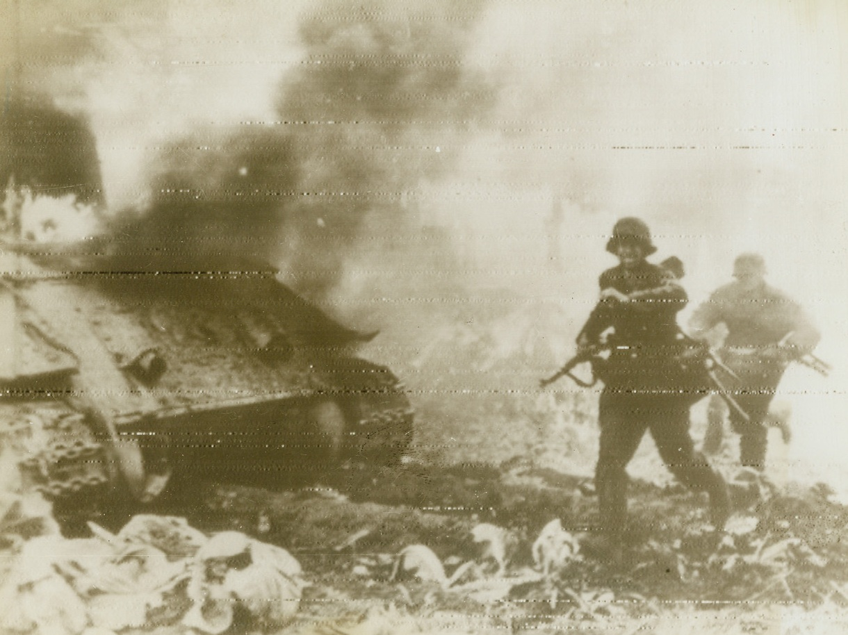 In the Midst of Battle, 8/23/1944. On the Russian Front—A German Panzer Grenadier dashes past a flaming tank during bitter fighting on the Eastern front. The tank was blasted by Russian trench mortar fire. Photo radioed to New York today (8/23) from Stockholm.  Credit: ACME radiophoto.;