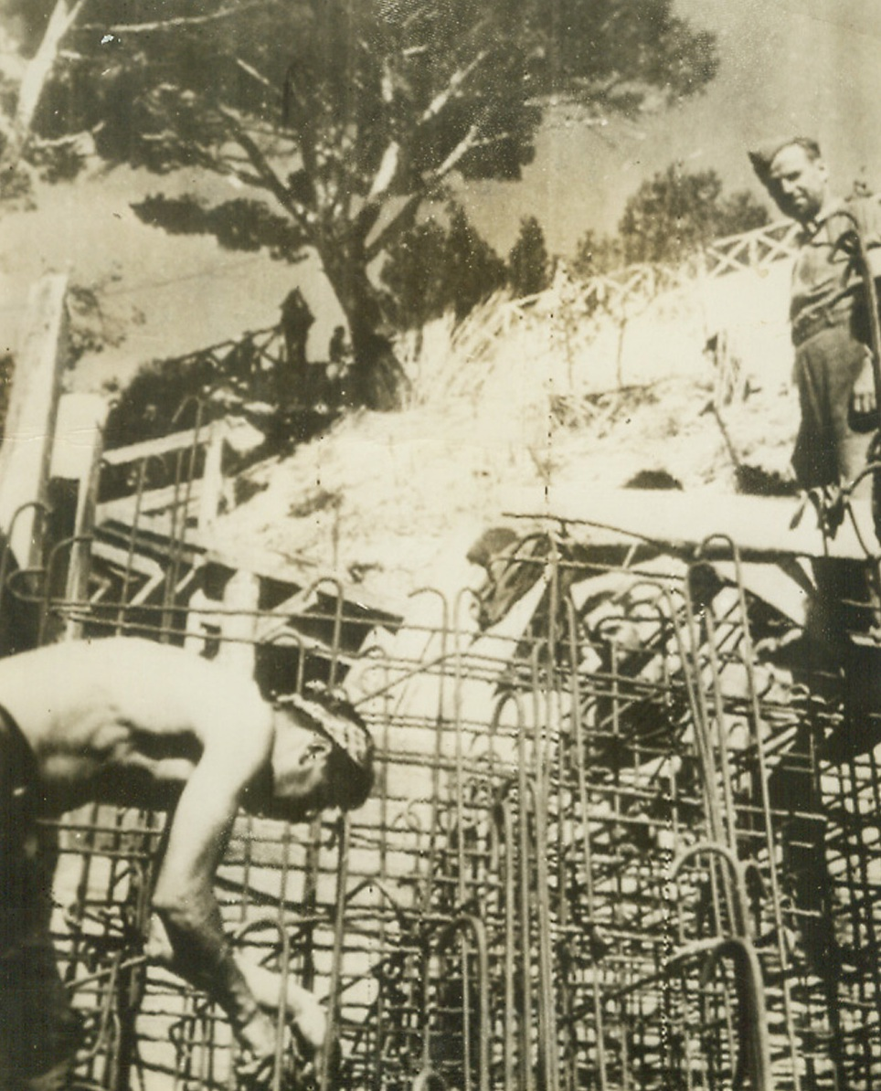 """Defenses That Failed, 8/16/1944. France—The German caption describes this photo as """"men working on partially completed Nazi defenses along the French Mediterranean coast"""" where Allied forces staged their surprise landings on August 15th, meeting no united resistance. Photo was radioed toNew York from Sweden today. Credit: ACME radiophoto.;"""