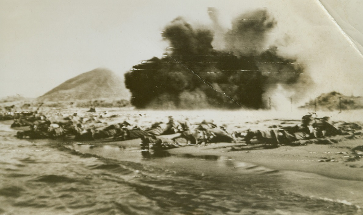 """Invasion Practice for Yanks, 8/15/1944. U.S. Infantrymen lie flat on their faces in the sand, as their Bangalore torpedoes explode, shredding """"enemy"""" barbed wire barriers along this """"invasion"""" beach. This scene was, and is being reenacted along the shore of Southern France, as Allied forces pour ashore to establish the fourth front. Credit: Army radiotelephoto from ACME.;"""