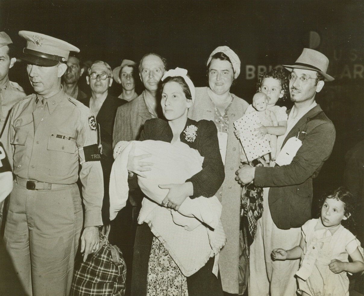 Free and Happy, 8/4/1944. Hoboken, New Jersey -- Headed for the train that is to carry them to Fort Ontario near Oswego, New York, is this family, part of almost 1,000 refugees from Italy who will remain in this country for the duration of the war. They are (left to right): Mrs. Netta Rothchild, holding her four-weeks old daughter Gratzia; and Mr. Isreal Rothchild, carrying his daughter Reneta as another daughter, Fanny, walks beside him. Credit: ACME;
