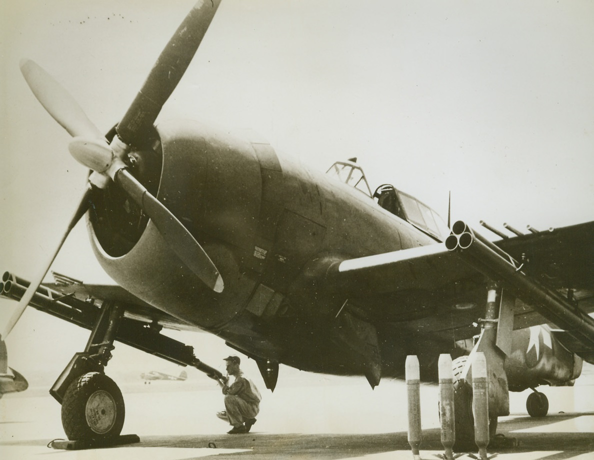 Thunderbolt Bristles with Guns, 8/1/1944. A soldier loads a projectile into the rocket armament of the far wing of a P-47 Thunderbolt. This plane is a deadly weapon of war with its eight .50 caliber machine guns and new rocket armament. Here is a closeup of the plane with its machine guns and the rocket gun armament under both wings. Three of the rockets are standing on end before a wheel of the plane. Credit: USAAF photo from ACME;
