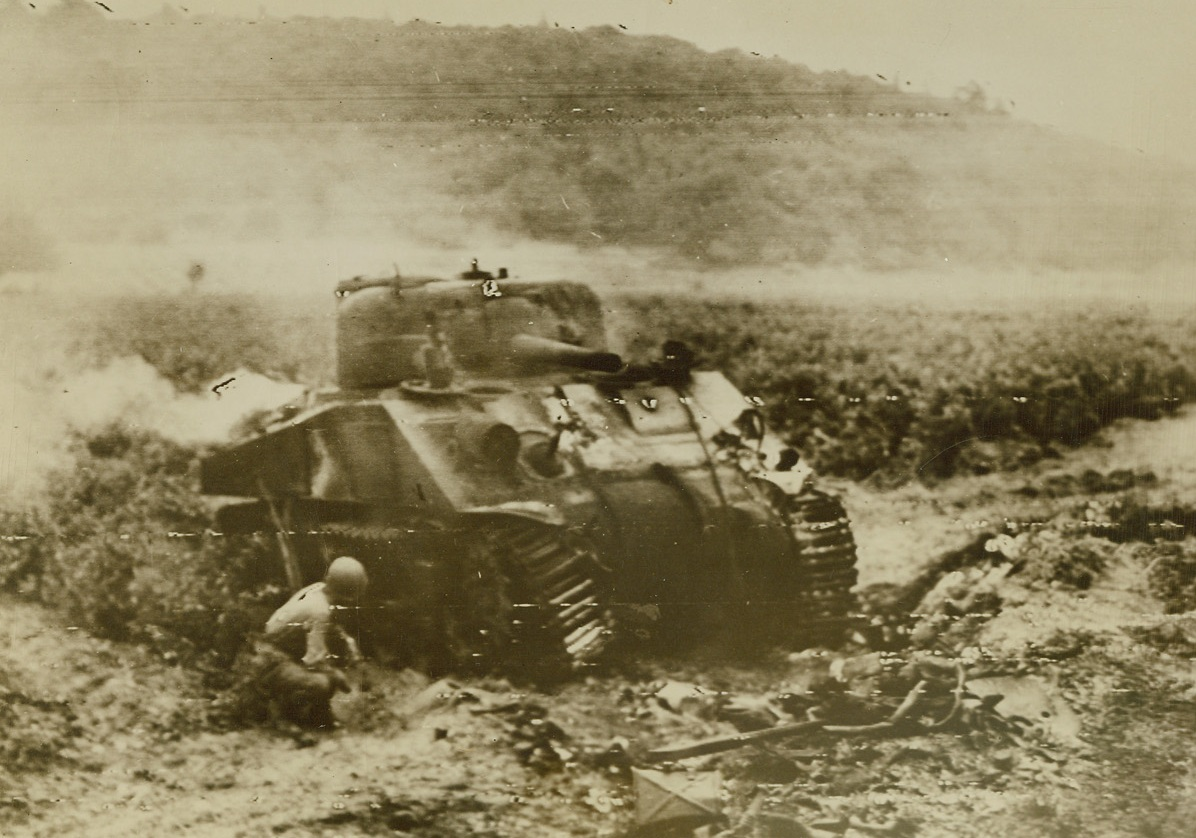 Almost a Rarity, 8/20/1944. Southern France -- A Sherman tank, which has been knocked out by a German 88, burns in a field near a town in Southern France. A U.S. soldier seeks cover beside the smoking hulk. Credit: US Army photo from ACME;