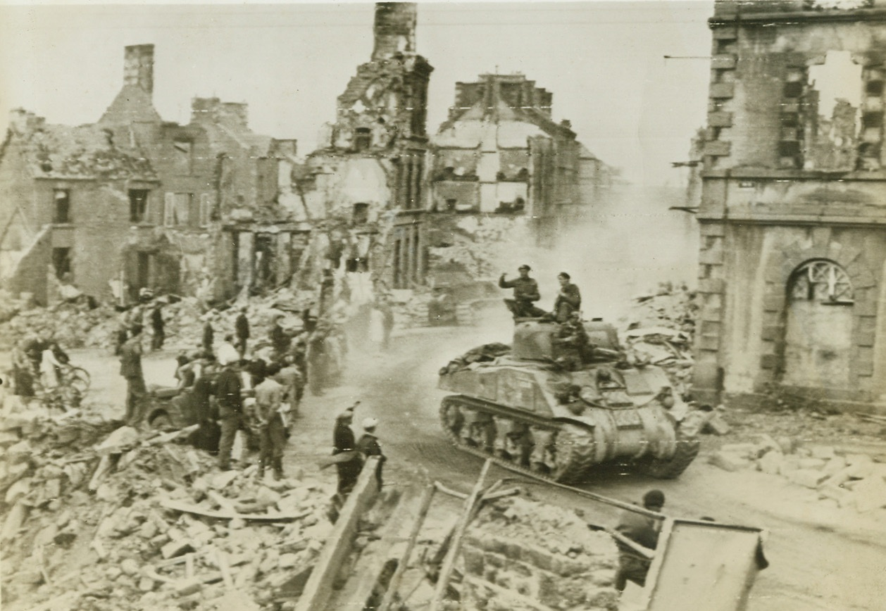 """Enroute to Pincer the Germans, 8/20/1944. Flers, France -- Townspeople in the bomb-wrecked, shell-ridden town of Flers line the streets to cheer British soldiers who move on in their """"General Sherman"""" tanks to close the gap at Falaise and trap the German forces fleeing toward Paris. This is a British War Office photo. Credit: US Army photo from ACME;"""