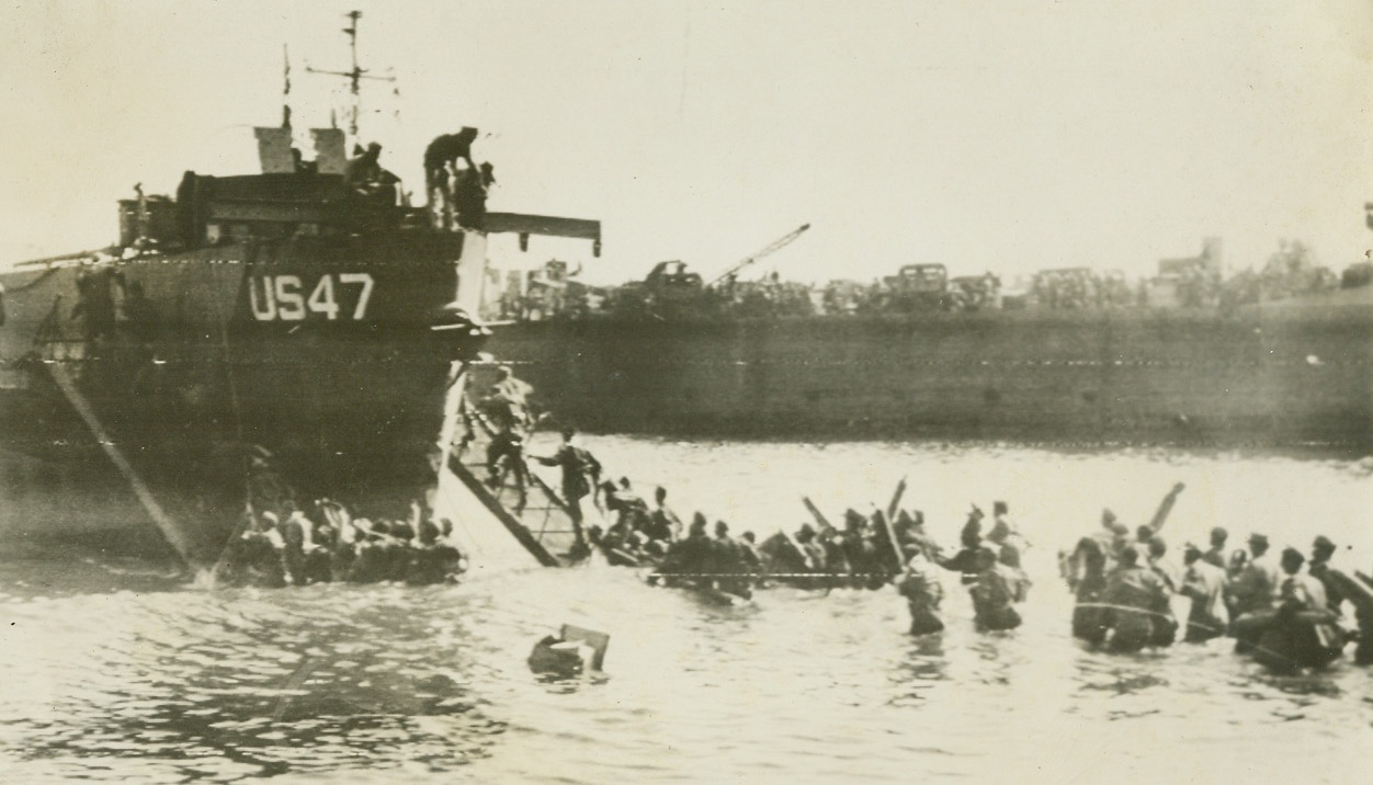 EVACUATE NAZI PRISONERS FROM S. FRANCE, 8/18/1944. FRANCE – Wading waist deep in water, long lines of Nazi prisoners are herded onto landing craft for the trip to Allied prison compounds.  They are part of the 7,000 Nazis captured in the first few days of the invasion of Southern France.;