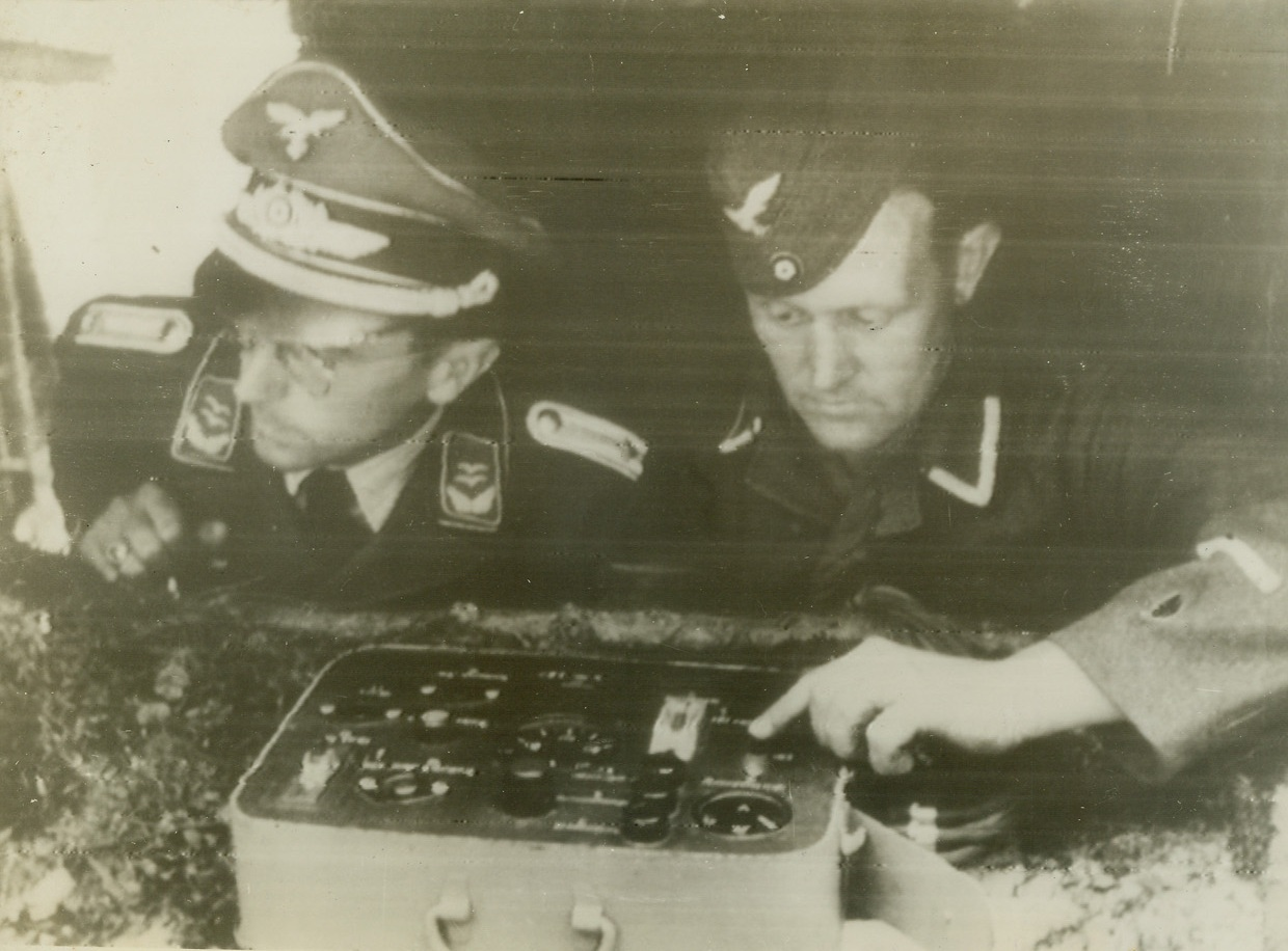 THE MEN BEHIND THE BOMBS, 8/17/1944. FRANCE – In this photo, radioed from Stockholm today (August 17), two Nazi soldiers, one with his finger on the button, are operating the switchboard which releases the flying bombs somewhere in France.  According to the German caption, the bombs are being directed against London.Credit: Acme;