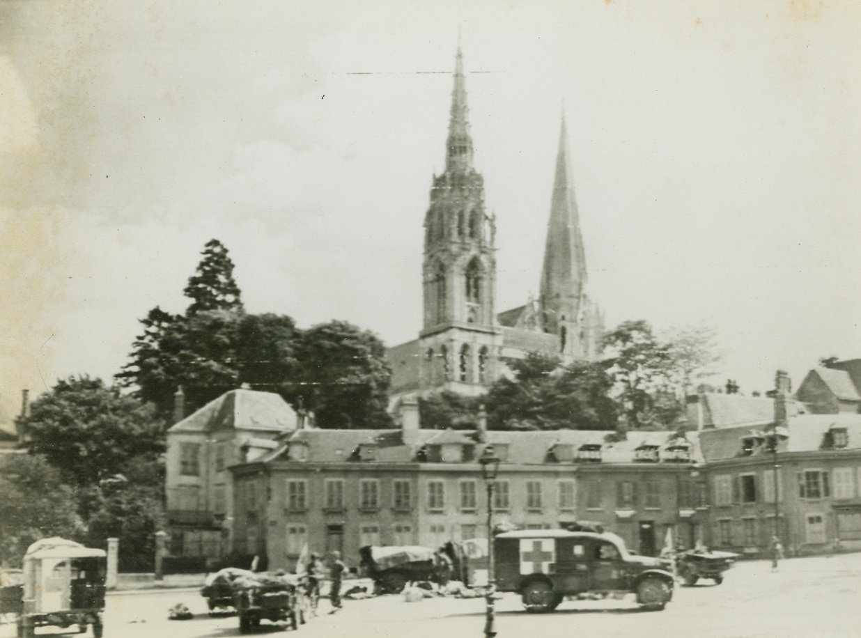 YANK MEDICS AT WORK IN CHARTRES, 8/22/1944. FRANCE - - Working in the shadow, of the famous 12th century Cathedral in Chartres, Yank medics give aid to wounded before continuing the push Eastward toward and beyond the Seine. Credit: Army Radio telephoto from Acme;