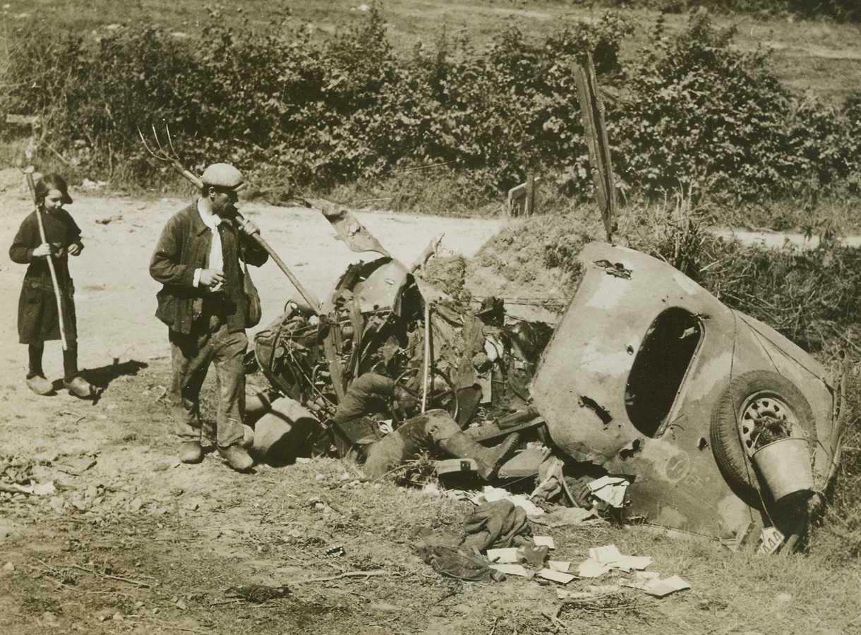 GRIM REMINDER OF WAR, 8/22/1944. MORTAIN, FRANCE – On their way to the fields this French peasant and his little girl pass a Nazi staff car and its dead driver, caught by shell fire at a crossroads near Mortain.  Accustomed to such sights, the two give it only a passing glance.Credit: Signal Corps photo from Acme;