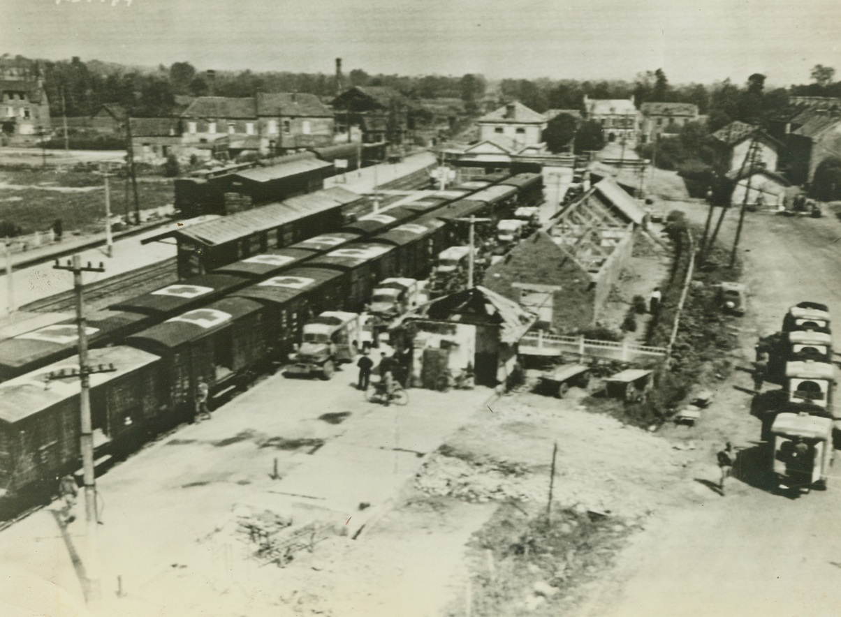 LOADING FIRST HOSPITAL TRAIN, 8/8/1944. FRANCE – The first allied hospital train to operate in France since D-day, is loaded with wounded from ambulances, at Lison.  The train is made up of boxcars left by fleeing Germans. Wounded are taken to Cherbourg on their way to England.  Credit: Army radio telephoto from Acme;