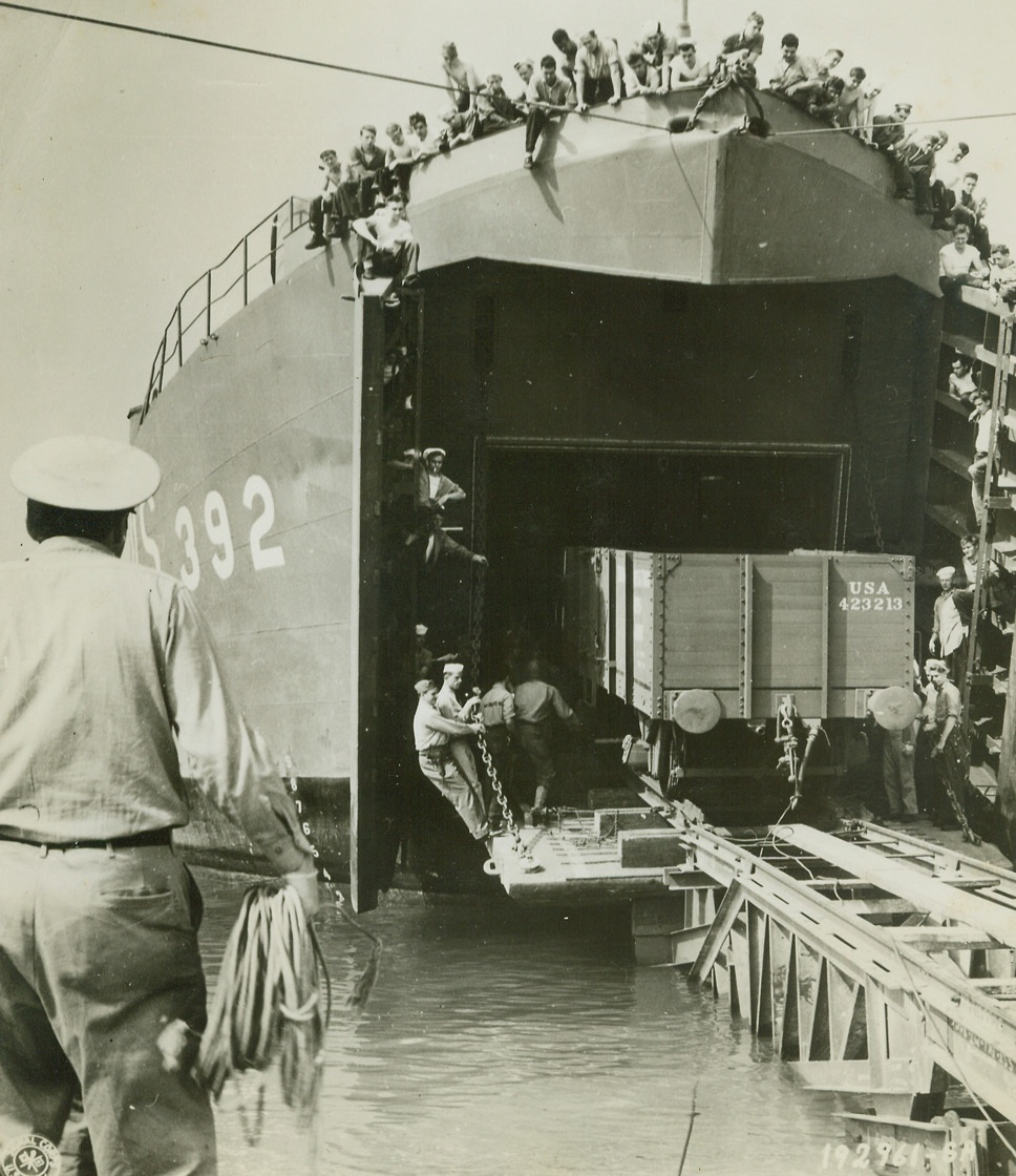 TAKE A TRAIN FROM A BOAT, 8/29/1944. FRANCE – In the first such attempt ever made, freight cars are brought ashore at Cherbourg harbor from an LST.  A specially constructed ramp made of railway tracks, facilitates the job. Credit: Signal Corps photo from Acme;