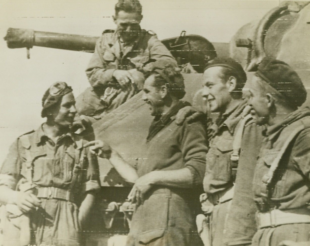 POLISH TROOPS JOIN ALLIES IN FRANCE, 8/15/1944. FRANCE – This photo, the first of its kind, shows Polish troops in action with the British and Canadian soldiers on the Normandy front.  Sgt. McVay (2nd from left), shares a joke with Polish comrades before setting off to join the attack South of Caen. Credit: British War office photo via army radio telephoto from Acme;