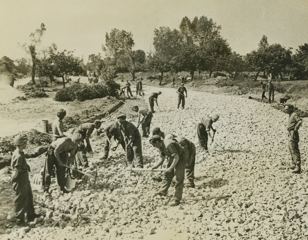 TO KEEP 'EM ROLLING, 8/15/1944. FRANCE – British Royal Engineers, using stone from damaged buildings and flint limestone from the stock of a former German factory near Colombelles, repair a stretch of road near that city. Credit: British official photo from Acme;