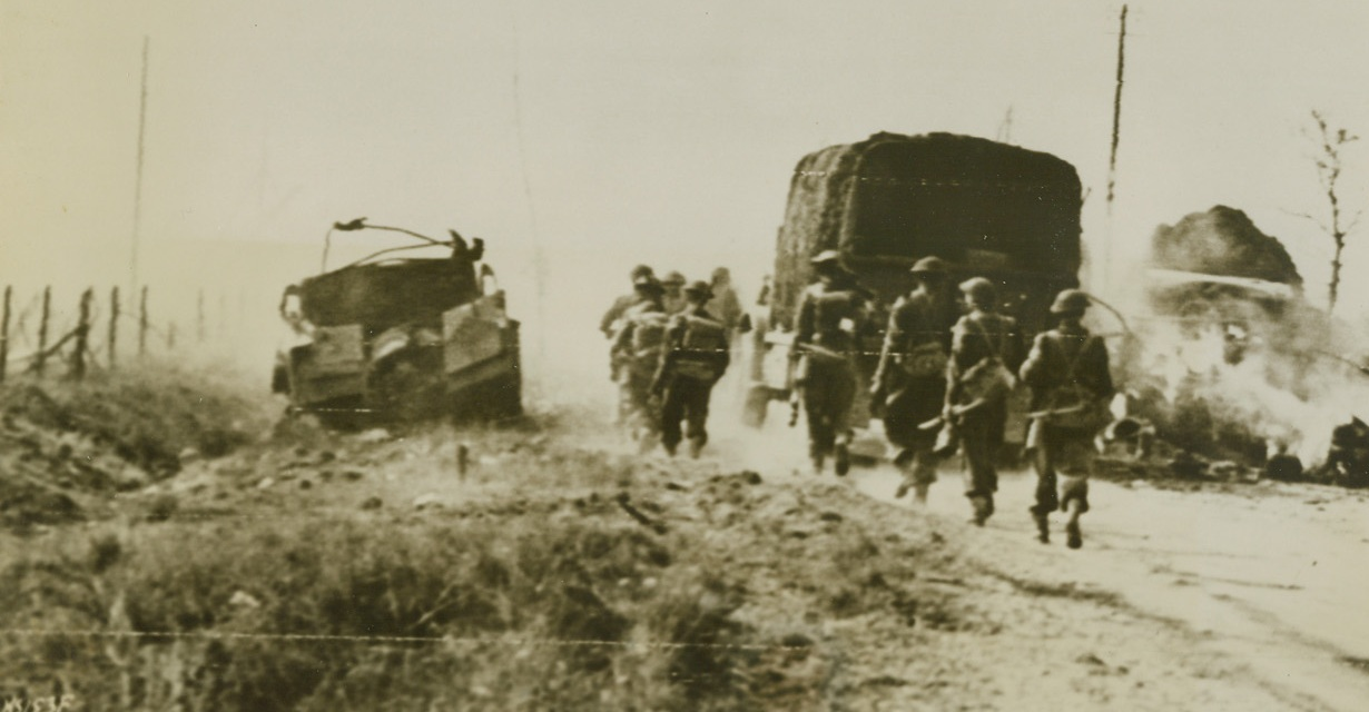 SOUTH TO FALAISE, 8/12/1944. FRANCE – Canadian infantrymen and army vehicles circle around a vehicle which has been knocked out by the side of the road, as the Canadian Army advances South on the road to Falaise. Credit: Canadian official photo via Signal Corps radio telephoto from Acme;