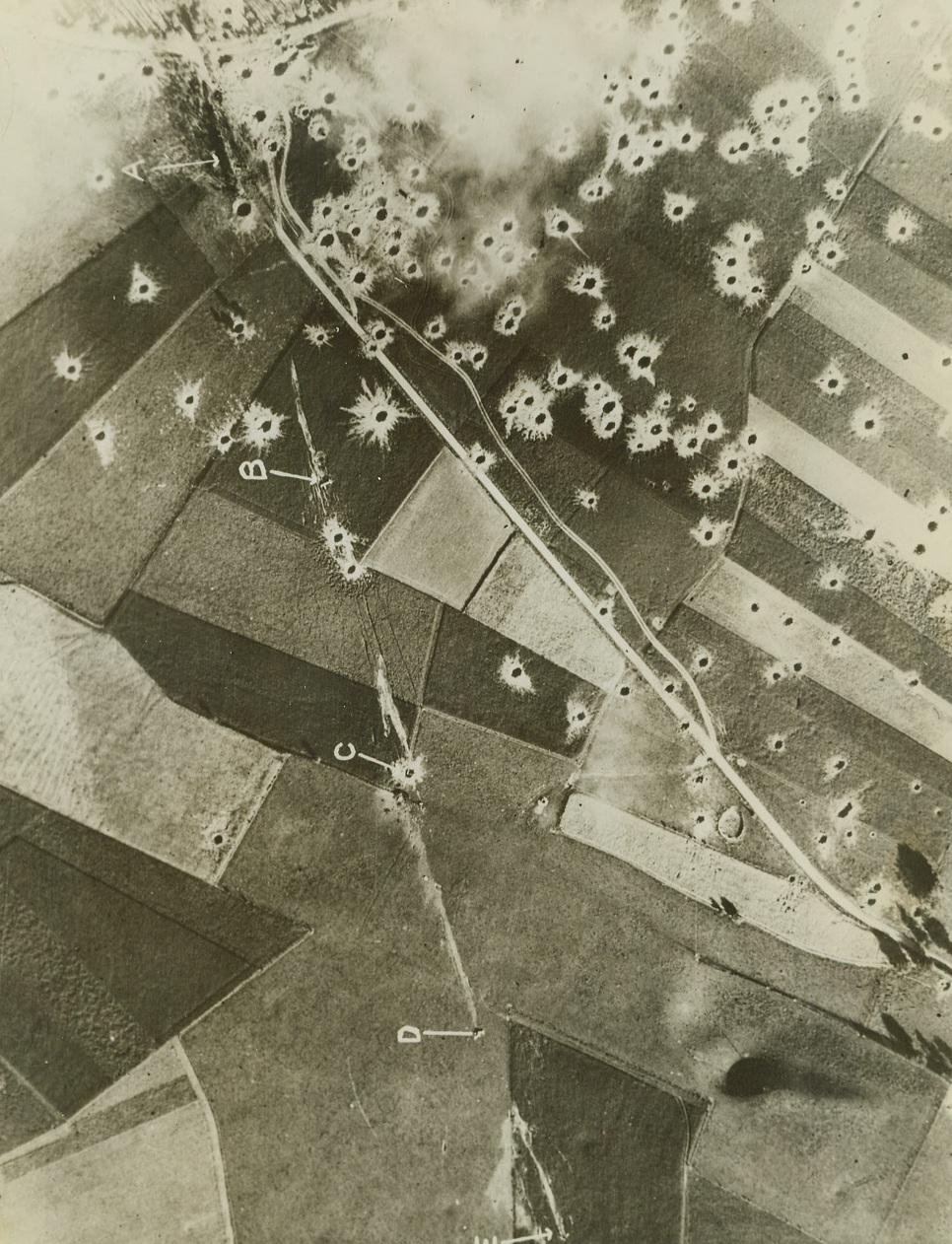 FLYING BOMB SITE BLASTED, 8/15/1944. FRANCE—A reconnaissance photo of a German Robot flying bomb site in the Pas de Calais area which has been attacked by Allied aircraft. Letter A, shows the launching platform surrounded by bomb craters. B,C,D, and E are flying bombs which have crashed on launching. Credit Line (British Official Photo from ACME);
