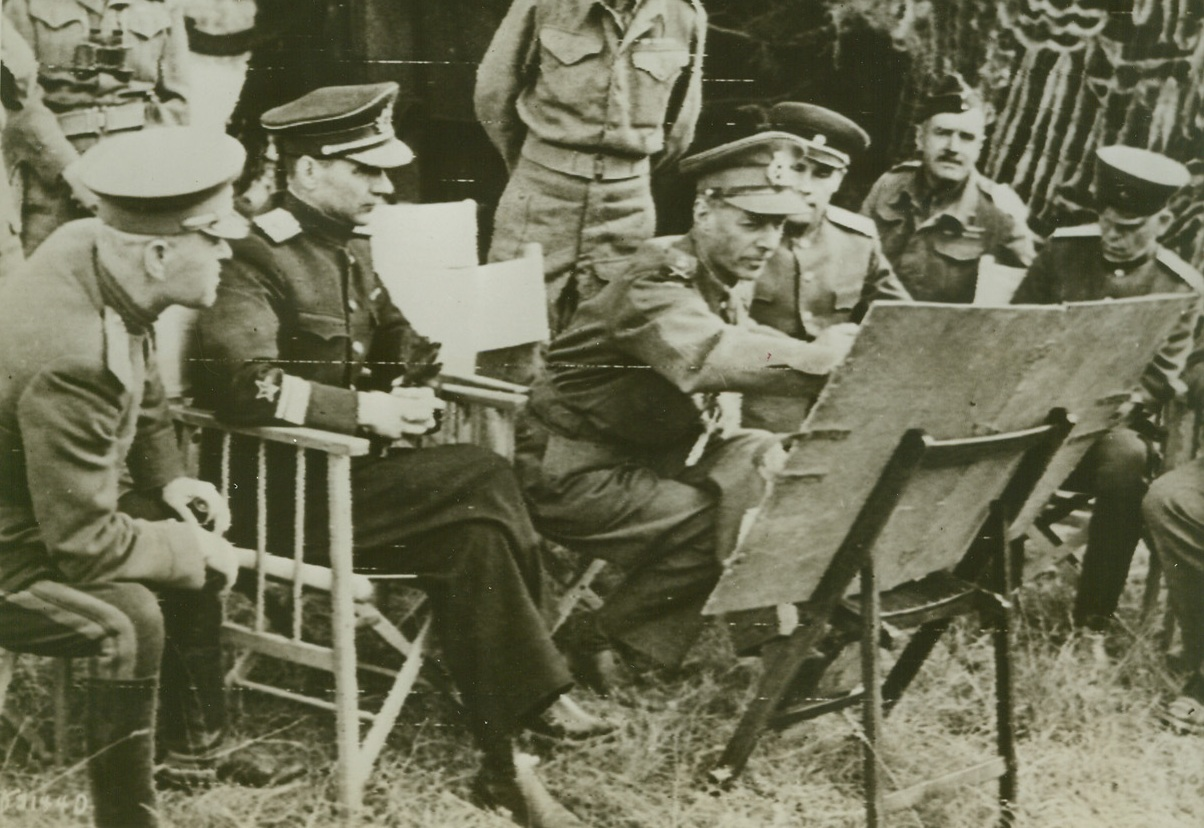 RUSSIAN MISSION VISITS BRITISH FRONT, 8/4/1944. FRANCE—A Russian Military Mission recently visited the British front in Normandy to get a first hand view of how the battles against the Nazis in the west are getting on. Seated as they hear an explanation of battle plans are (left to right): Col. Jorbarov; Vice Adm. Kharlamov; Lt. Gen. Dempsey, commander, British 2nd Army; Maj. Gen. Sklyarov; and Maj. Gen. Vasiliev. Credit (British Official Photo Via Army Radiotelephoto from ACME);