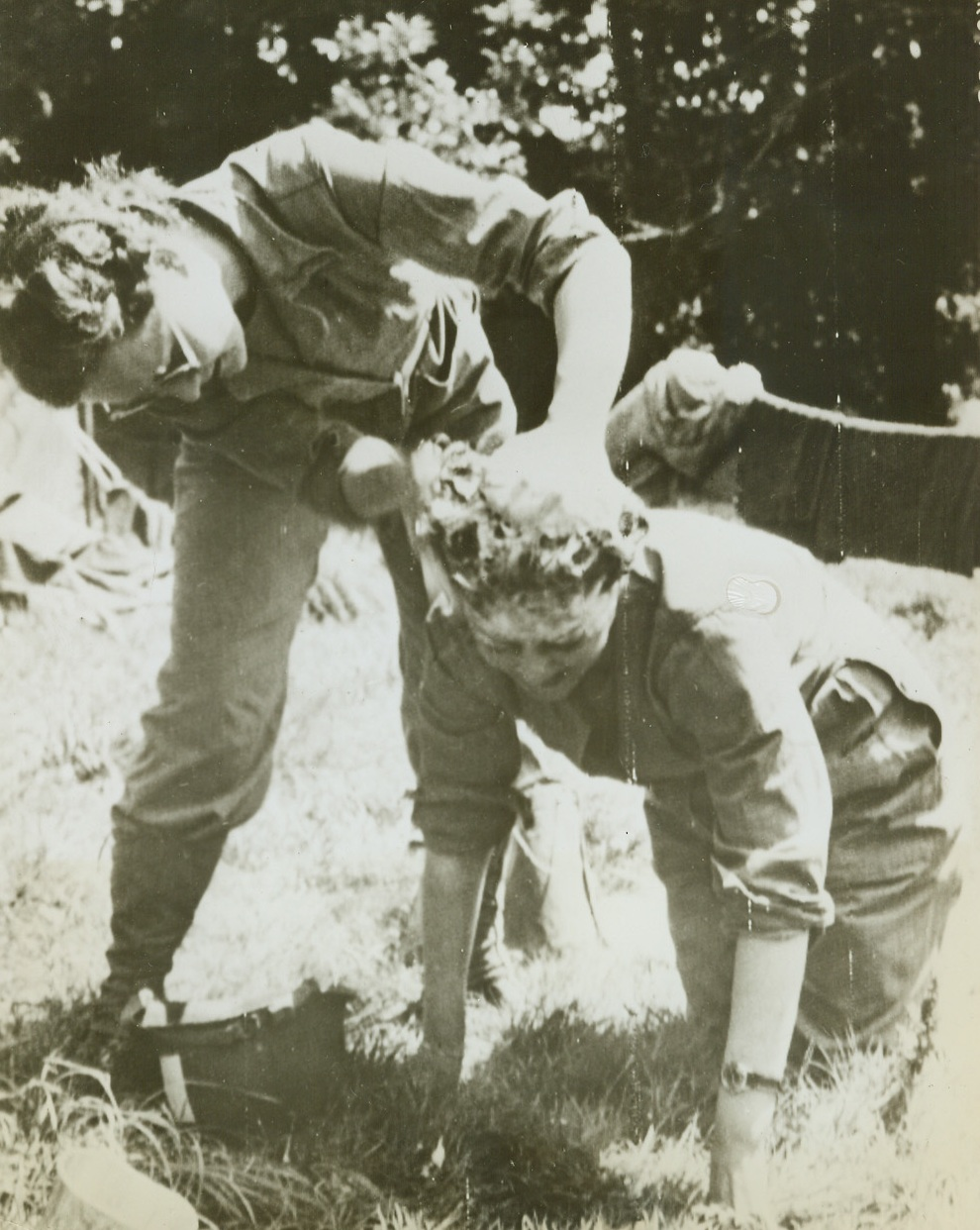 """""""SISTERS OF THE SUDS"""", 8/3/1944. FRANCE—Two WACS take turns washing each other's hair, with a GI helmet serving as a basin. They are: Pvt. Claire Dickman, of San Francisco, Calif. (left), and Selma Herfor, of New York City. Credit Line (Army Radiotelephoto from ACME);"""