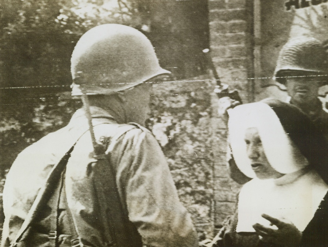 NUN GIVES YANKS INFORMATION, 8/2/1944. FRANCE—A French nun gives information about retreating German forces to Yanks, who pause on their way to the Avaranches front.  Credit (Signal Corps Radiotelephoto from ACME);