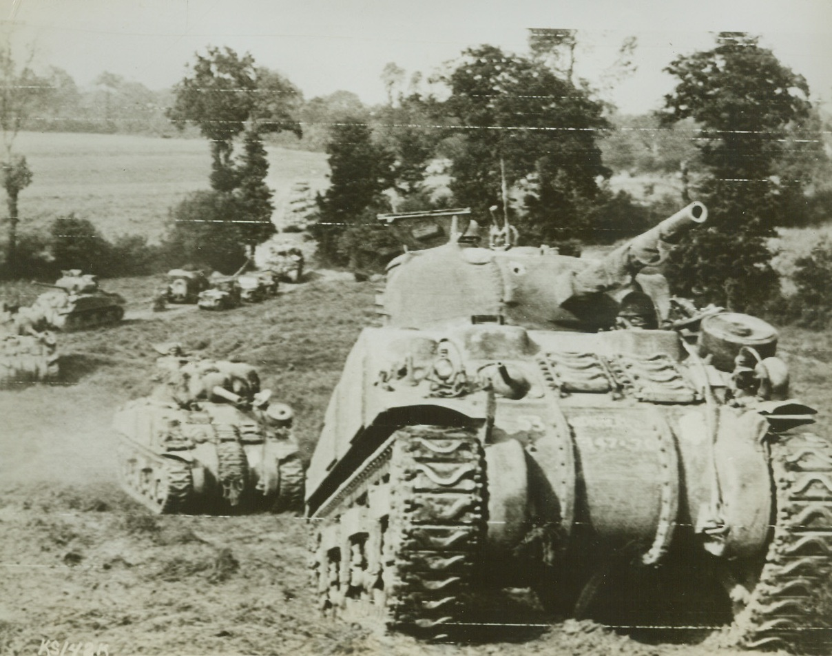 BRITISH TANKS MOVE UP TO FRONT, 8/2/1944.CAUMONT, FRANCE—A column of British-manned Sherman tanks move forward through a wooded area south of Caumont to take part in the heavy British offensive against the Germans in this section. Credit (British Official Photo via US Army Radiotelephoto from ACME);