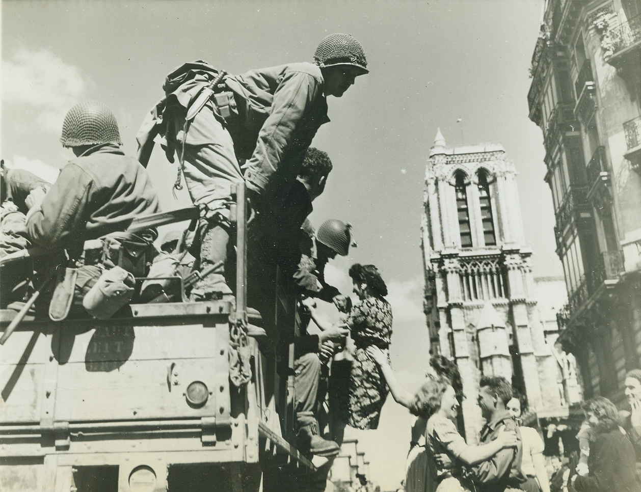 Welcome to the Liberating Americans, 8/28/1944. Paris – United States soldiers are shown being joyfully greeted by French women in the shadow of Notre Dame Cathedral. They dance – and one girl may be pulling a soldier from the truck. Credit: ACME photo by Bert Brandt for the War Picture Pool;