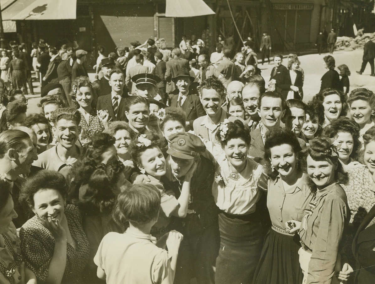 ACME Photog Gets Hugs And Kisses, 8/30/1944. France – Wildly enthusiastic French girls greet ACME Newspictures Photographer Bert Brandt with hugs and kisses as he entered Paris with the first group of liberating forces. Brandt's pictures of the freeing of the French capital, along with other ACME photographers' photos, were the first to reach the United States. Credit: ACME photo by Bert Brandt, War Pool Correspondent;