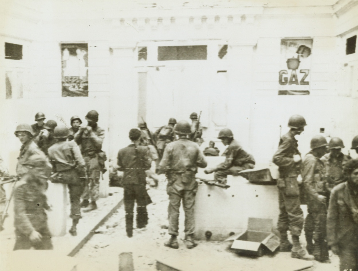 """""""Soup's On"""" in St. Malo, 8/17/1944. France – Americans gather in an empty store in the Breton town of St. Malo for chow. In the background, German prisoners are seated on the curb. In left foreground and just to left of center are two Spanish Loyalists (former leaders) now fighting with the Yanks. Credit: Army Radiotelephoto from ACME;"""